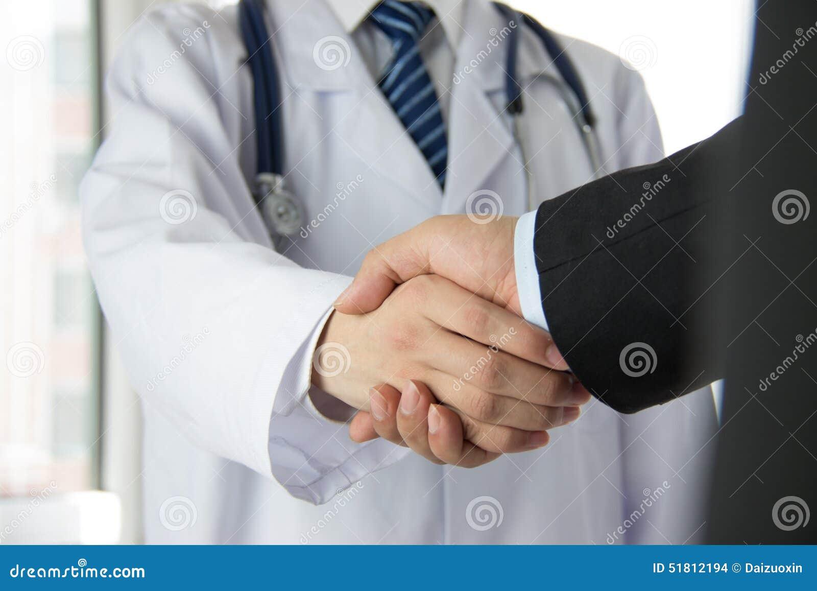 Doktor och affärsman som skakar händer