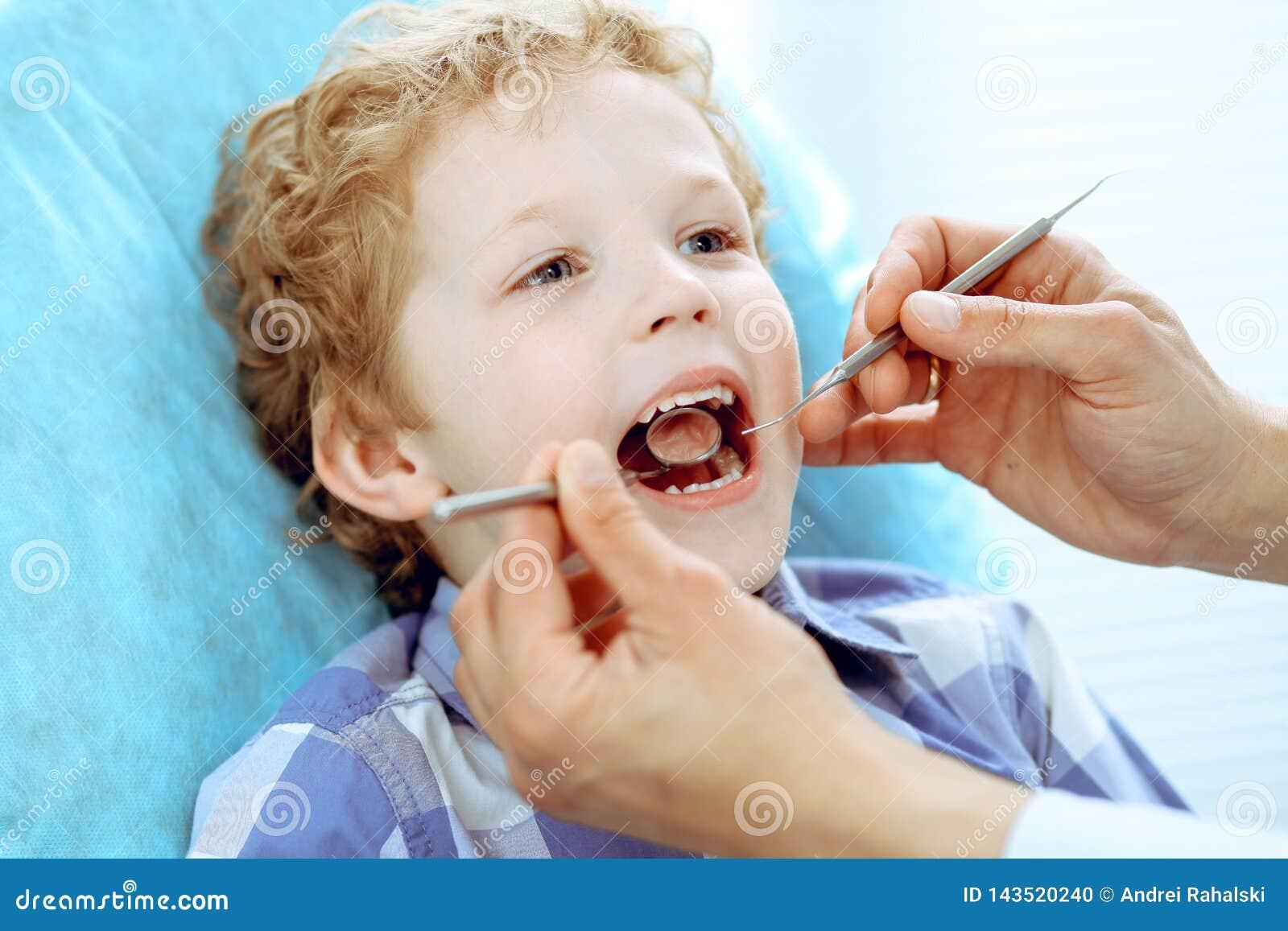 Doktor och tålmodigt barn Pojke som har hans tänder att undersökas med begrepp för tandläkare Medicine, hälsovård- och stomatolog
