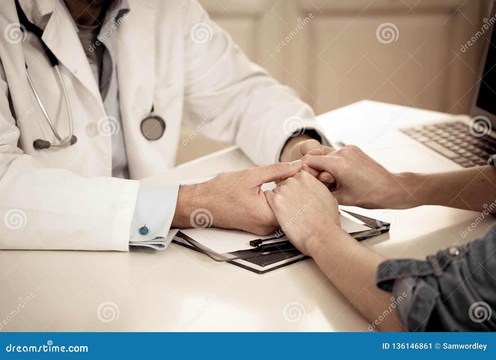 Doktor som rymmer kvinnliga tålmodiga händer med medkänsla och komfort för uppmuntran och inlevelse
