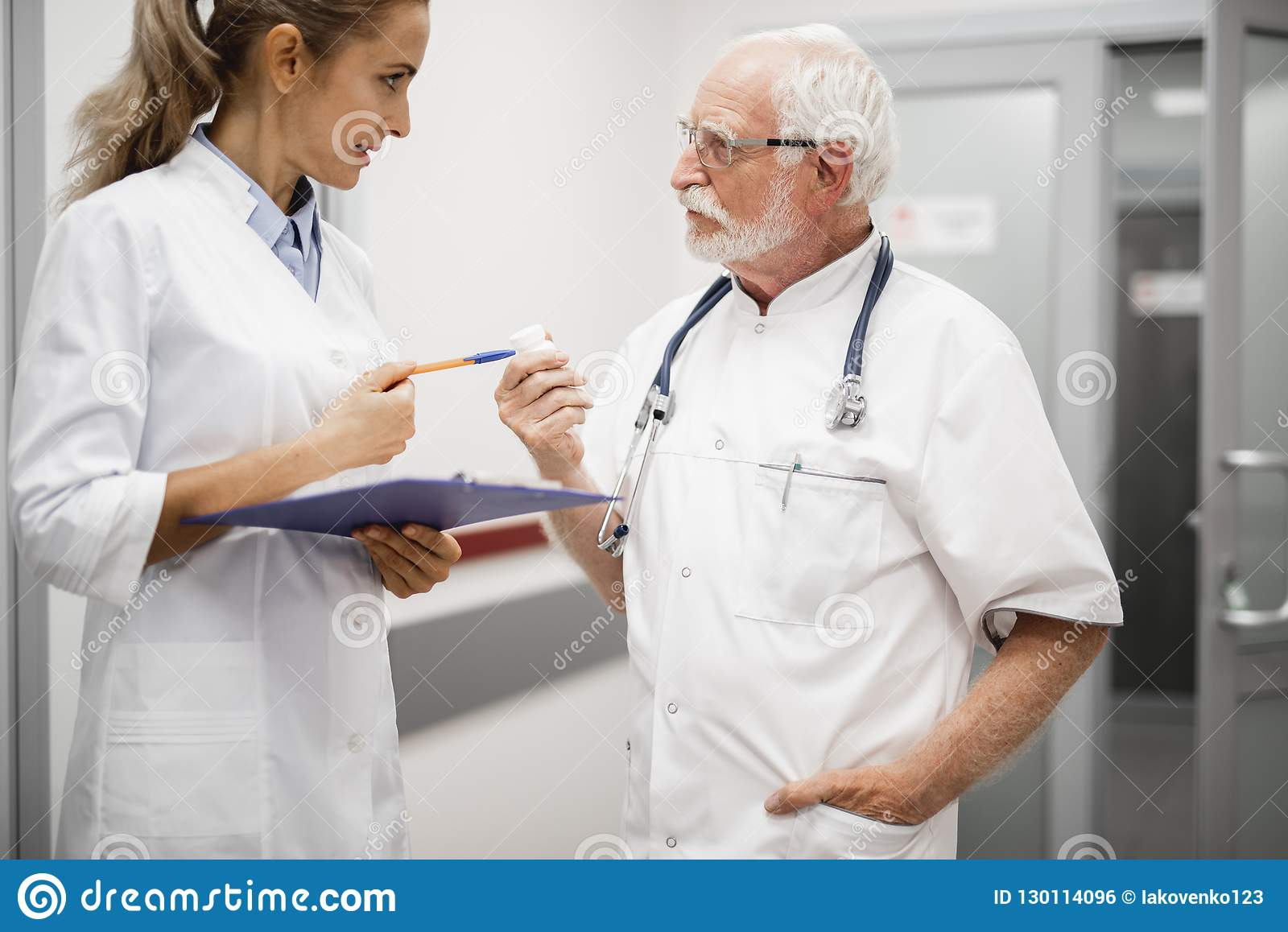 Doktor som talar med sjuksköterskan, medan rymma apotekflaskan med piller
