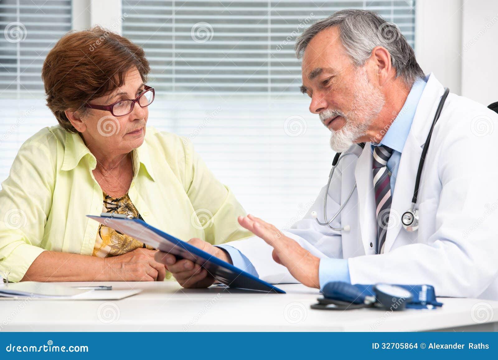Doktor som talar till hans kvinnliga tålmodig