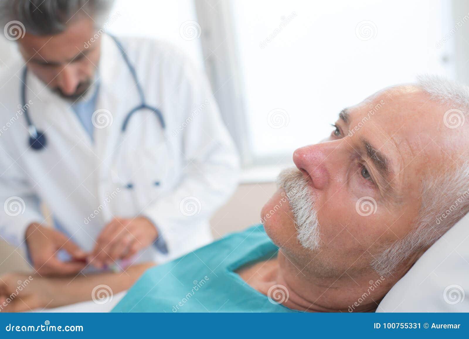 Doktor som tar blodtryck den manliga patienten i sjukhus