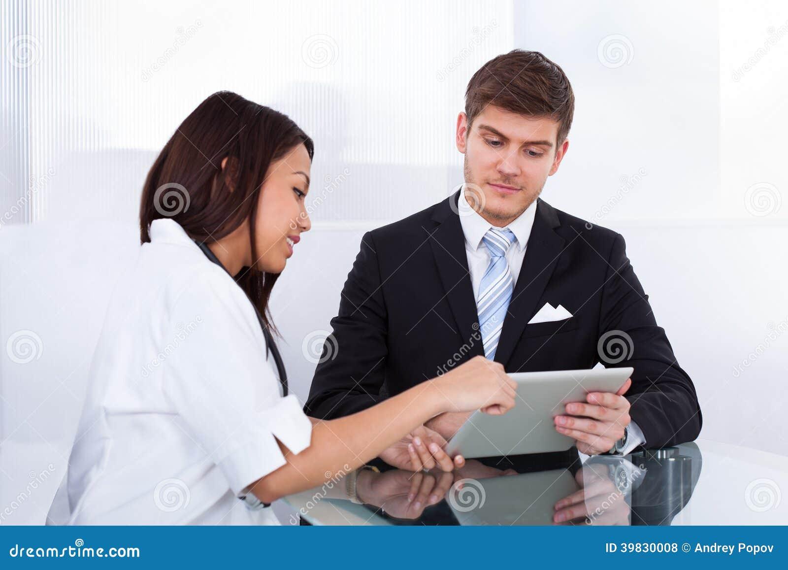 Doktor som visar den digitala minnestavlan till affärsmannen