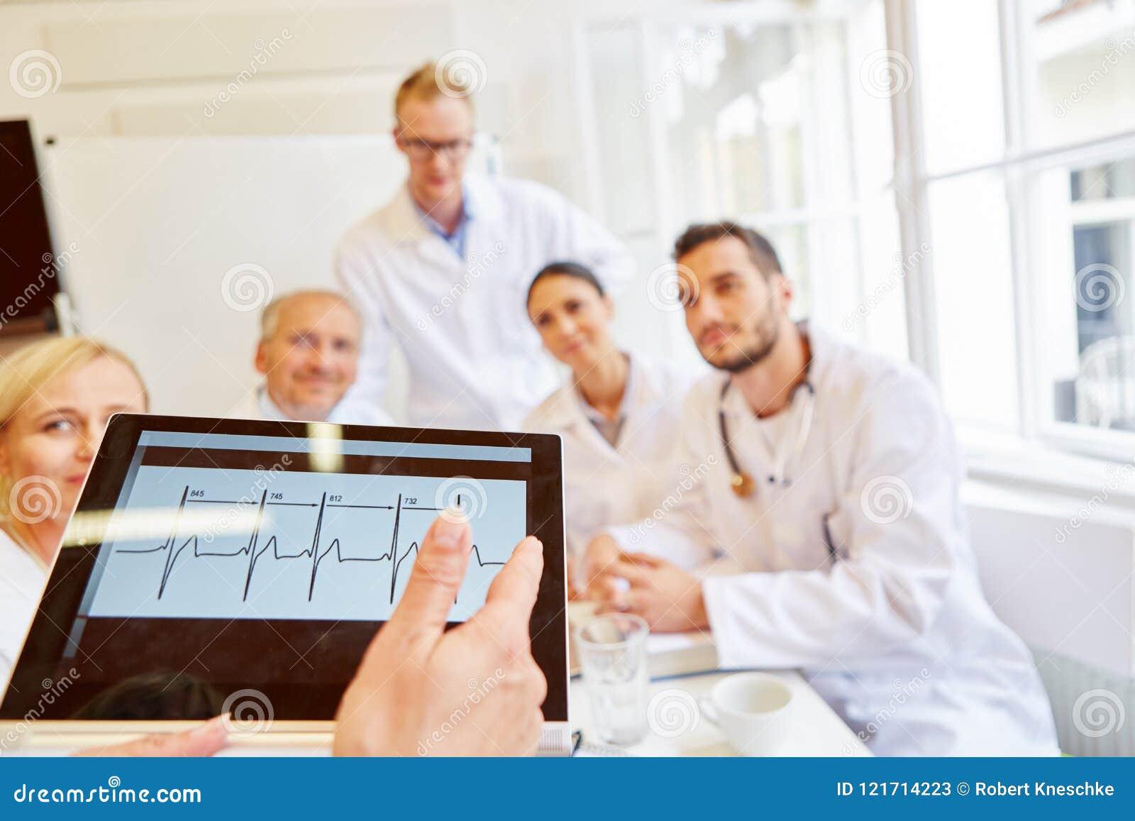 Doktorer som diskuterar att finna för ECG