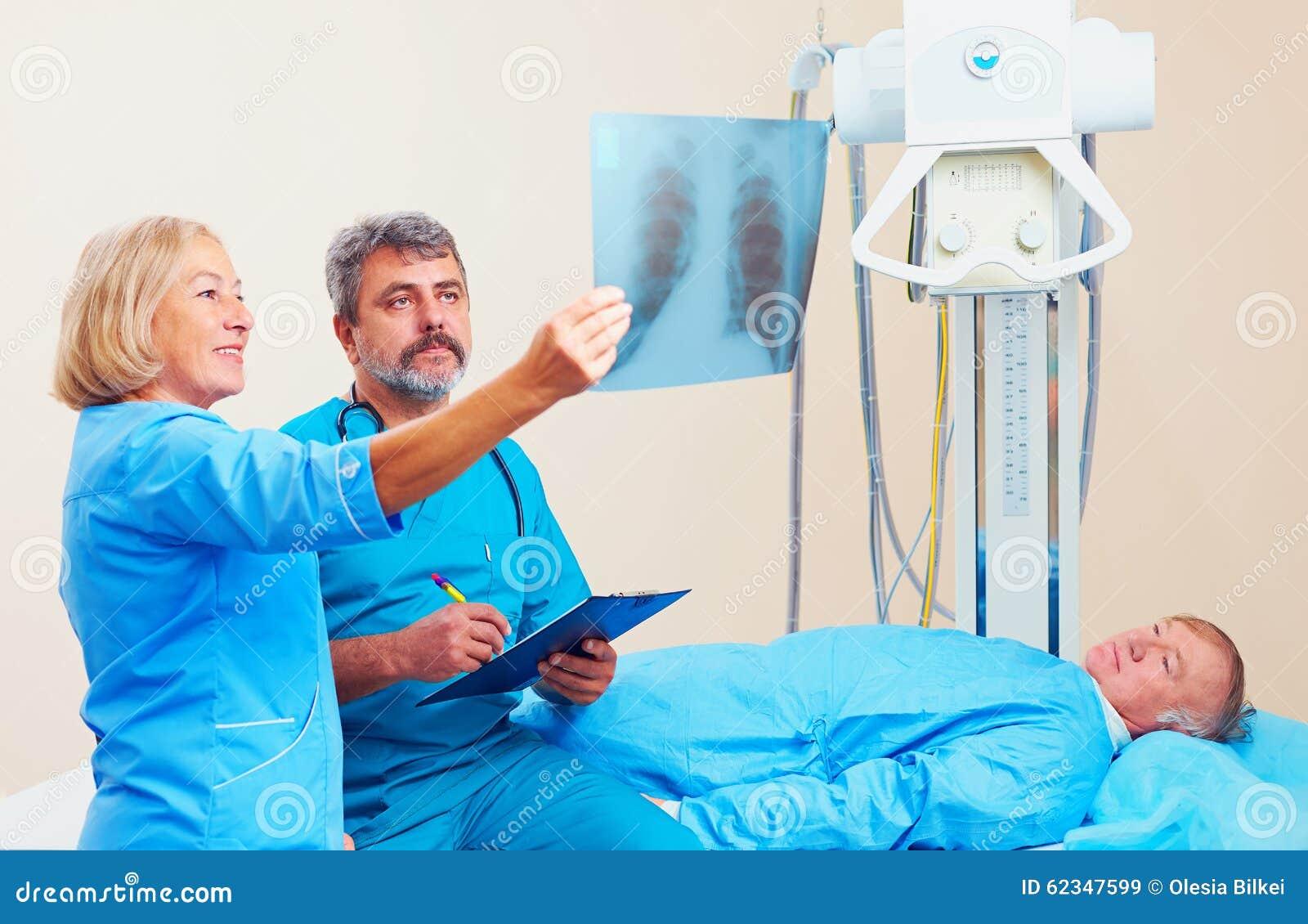 Doktorer som diskuterar den röntgen- radiotelegrammet i röntgenstråle, hyr rum med patienten