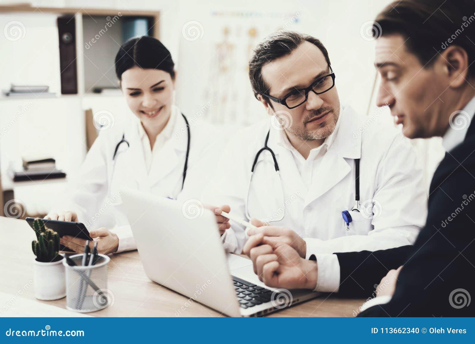 Doktorn i exponeringsglas råder tålmodigt sammanträde på tabellen med bärbara datorn i medicinskt kontor