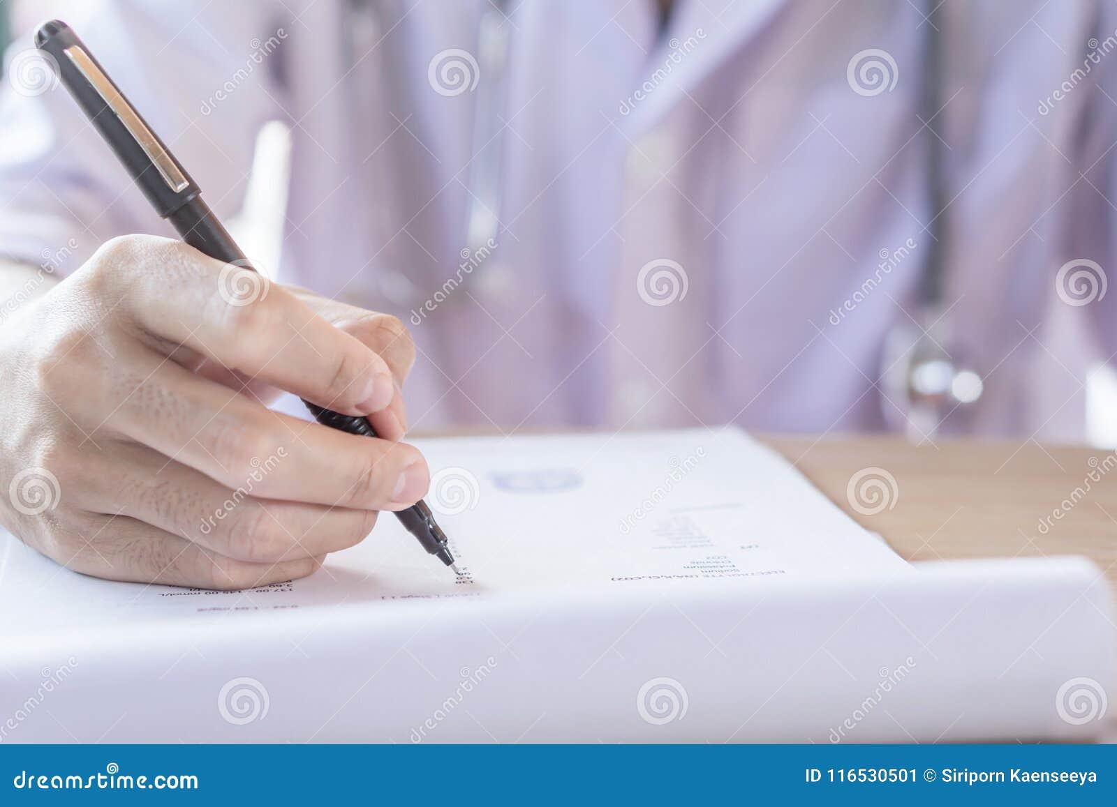 Doktorska ręka pisze recepcie na schowku