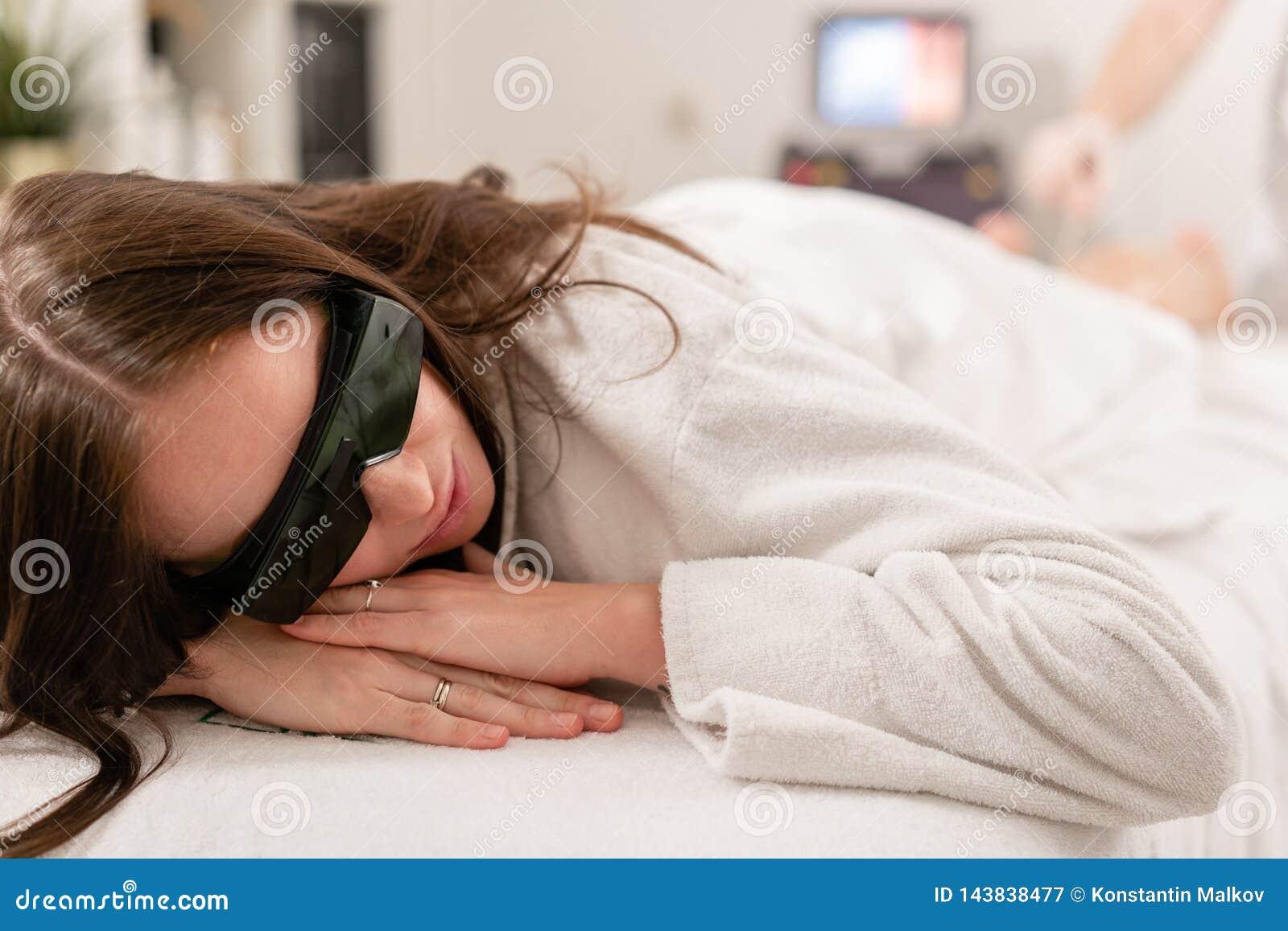 Doktorski cosmetologist robi procedurze m?odej dziewczyny brunetce Laserowa epilacja i kosmetologia W?osiany usuni?cie na damach