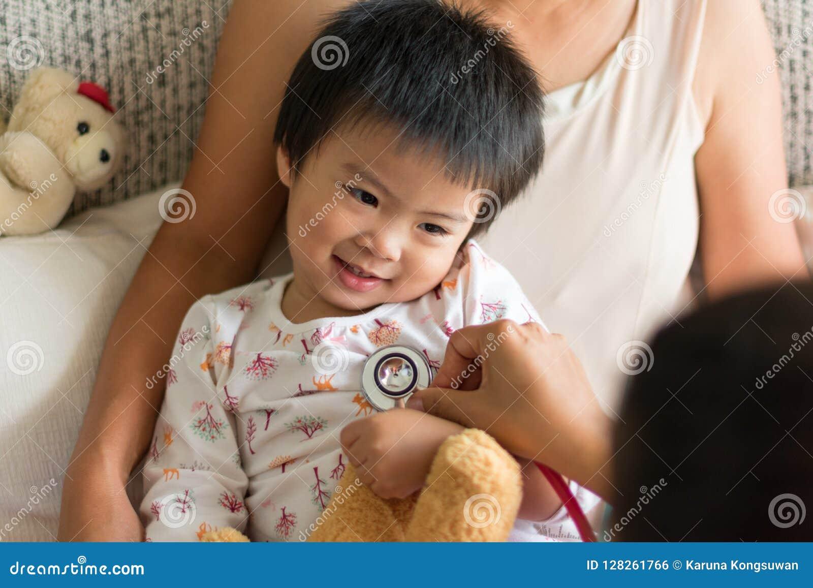Doktorski egzamininujący dziecko dziewczyny w szpitalu z jej mamą
