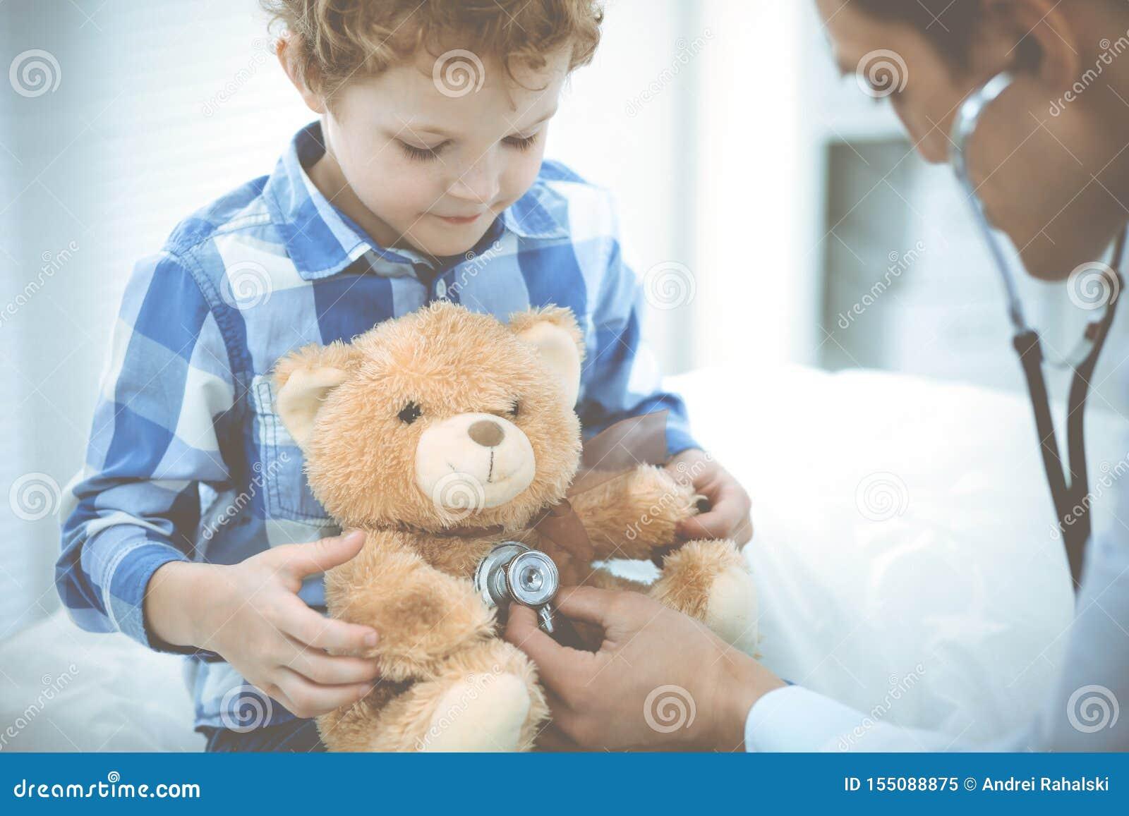 Doktorski i cierpliwy dziecko Lekarz egzamininuje ch?opiec Miarowa medyczna wizyta w klinice opieki zdrowie medycyna