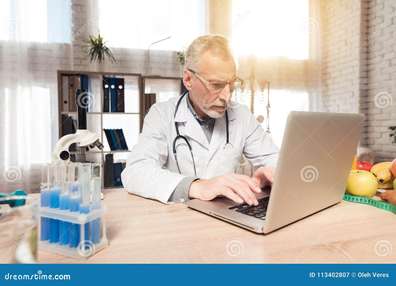 Doktorski obsiadanie przy biurkiem w biurze z mikroskopem i stetoskopem Mężczyzna pracuje na laptopie