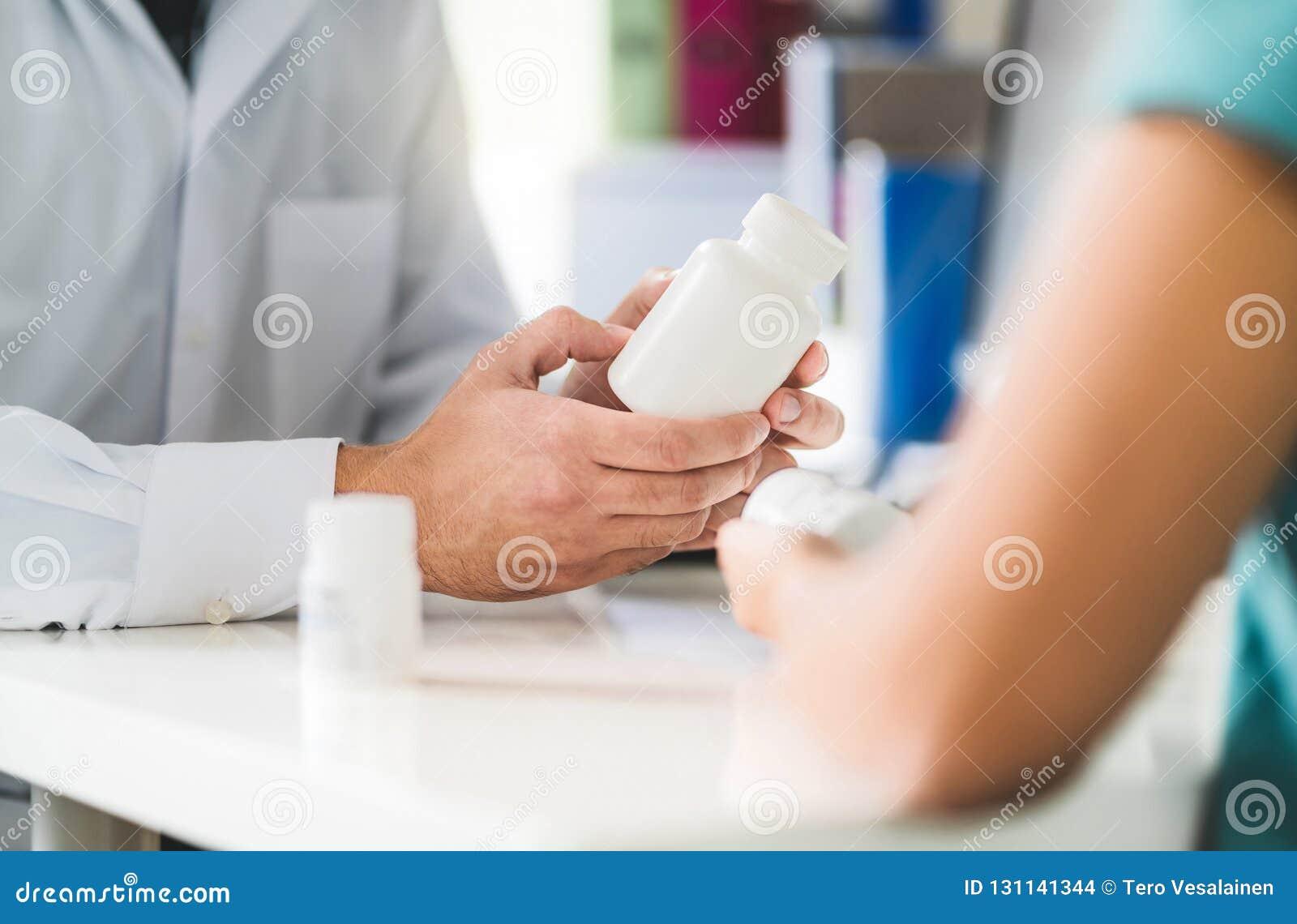 Doktorski ordynacyjny pacjent o prawym lekarstwie Lekarza mienia pigułki w ręce i medycyna