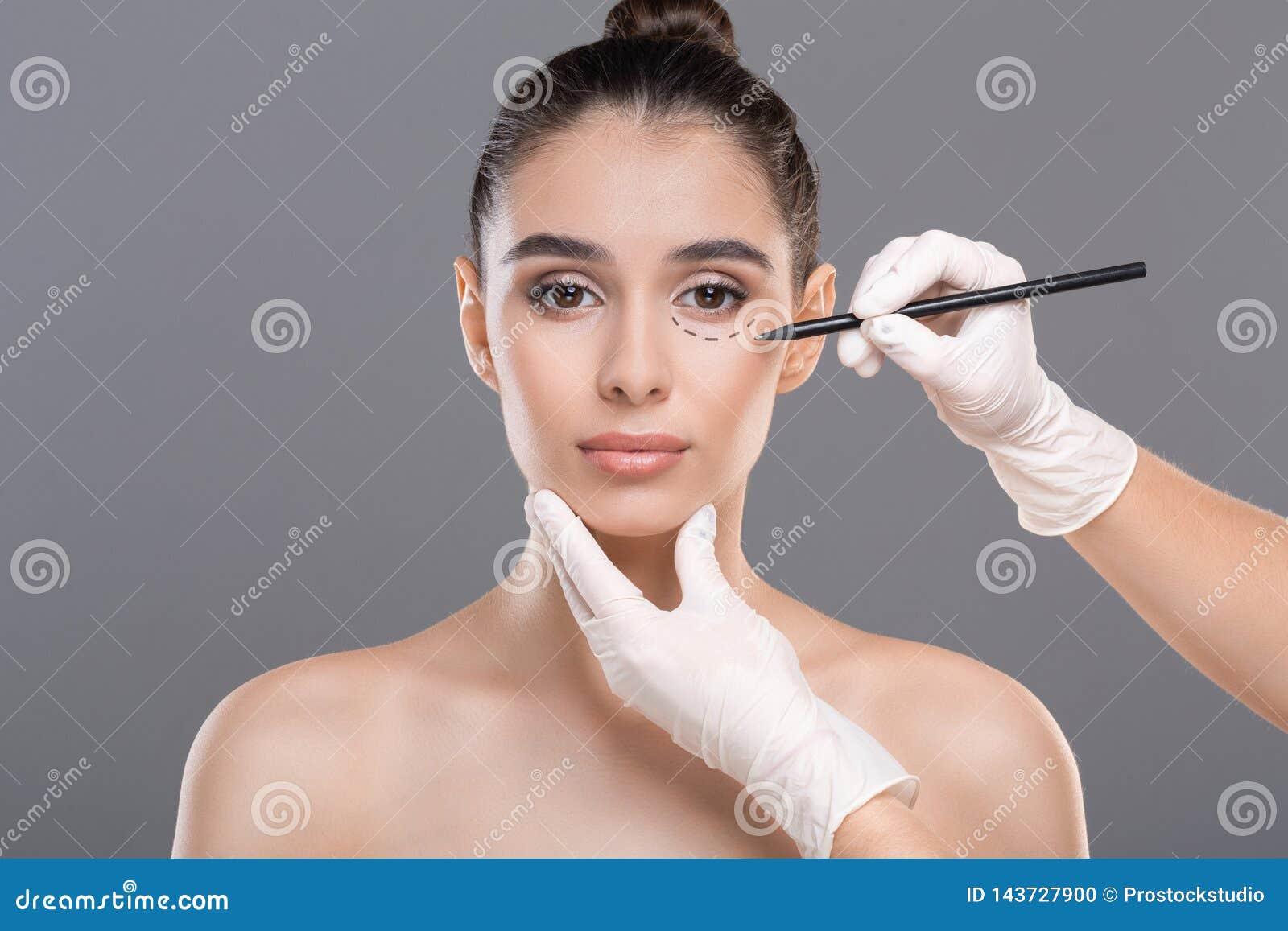 Doktorzeichnung markiert auf weiblichem Gesicht vor Verfahren