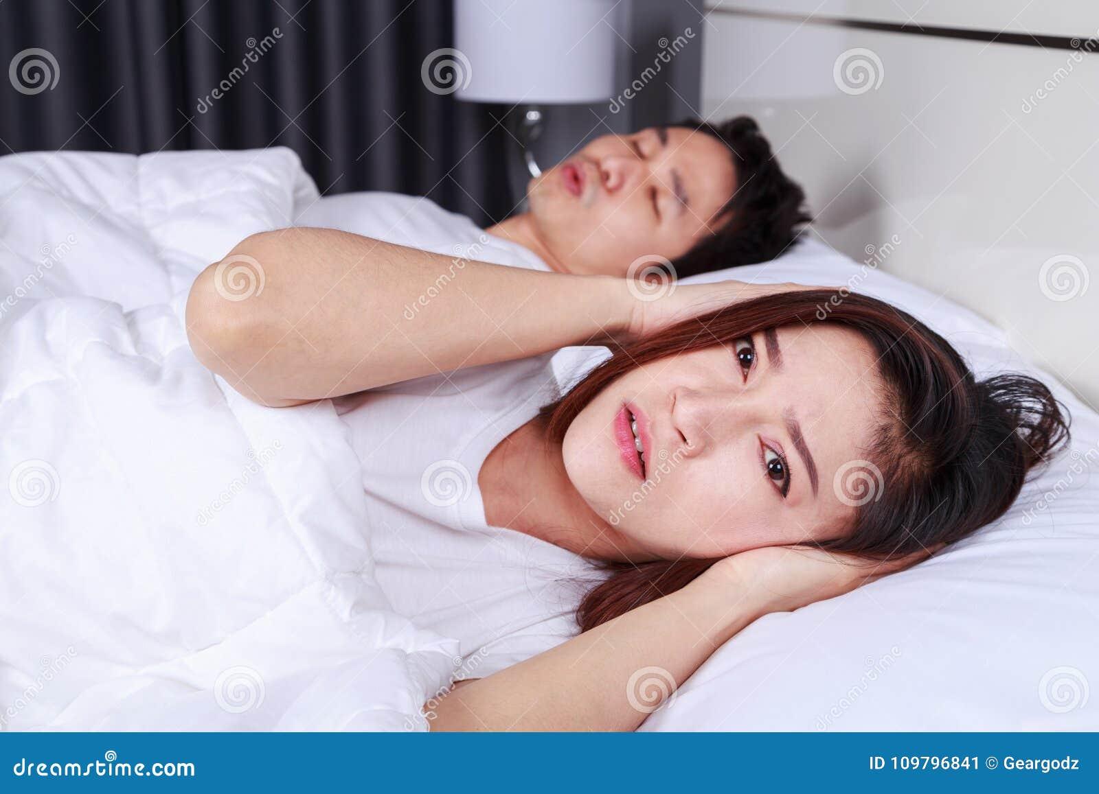 Dokuczająca żona blokuje jej ucho od hałasu chrapa wewnątrz mąż