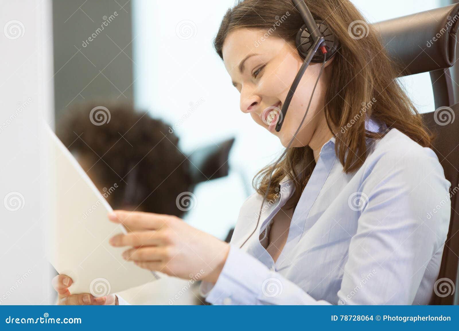 Dokumenterar den bärande telefonhörlurar med mikrofon för den unga affärskvinnan, medan läs-, i regeringsställning