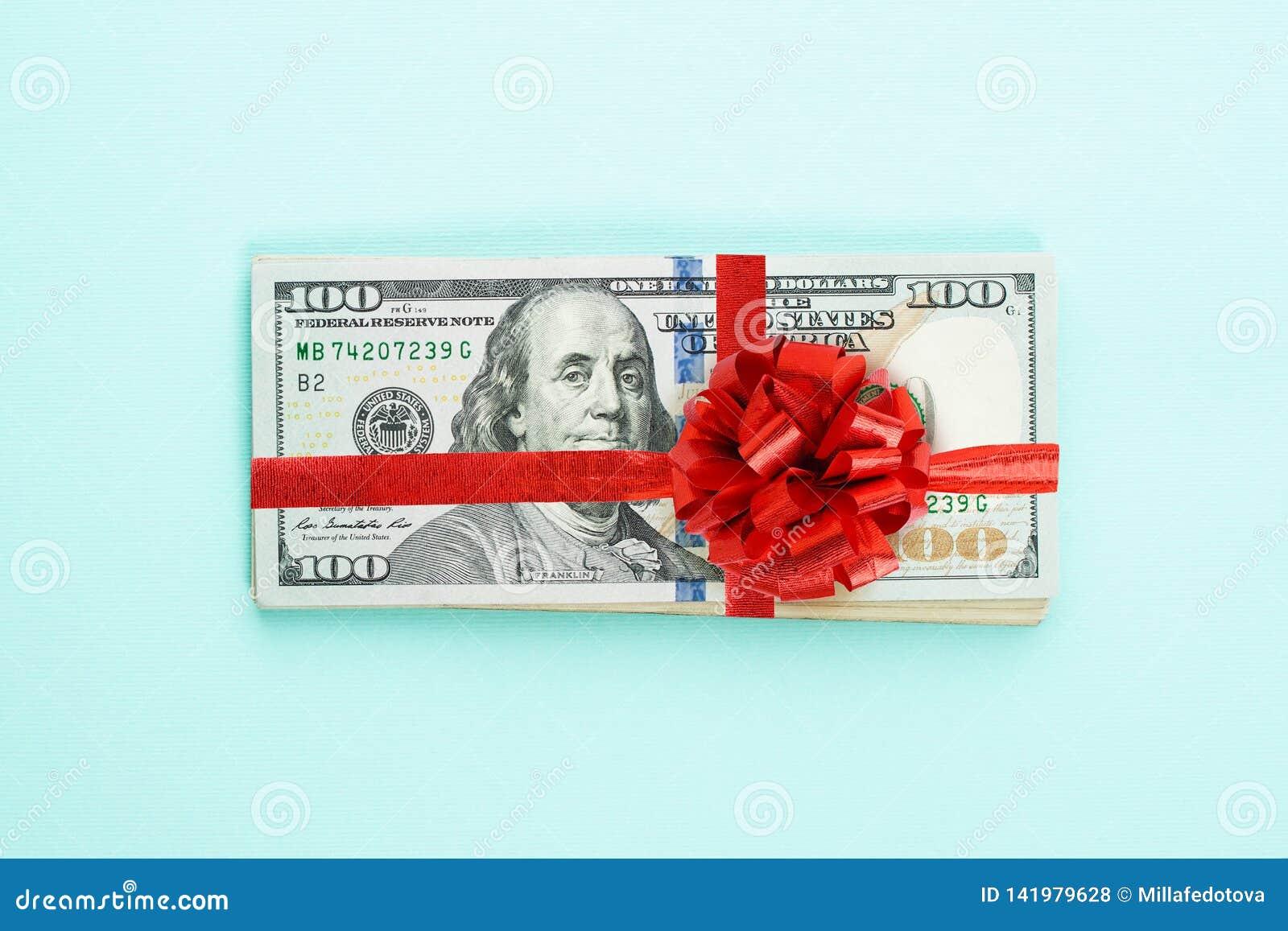 Dolara amerykańskiego pieniądze gotówki sterta z czerwonym faborkiem i łęk na błękitnym tle Amerykańscy dolary 100 banknotu preze