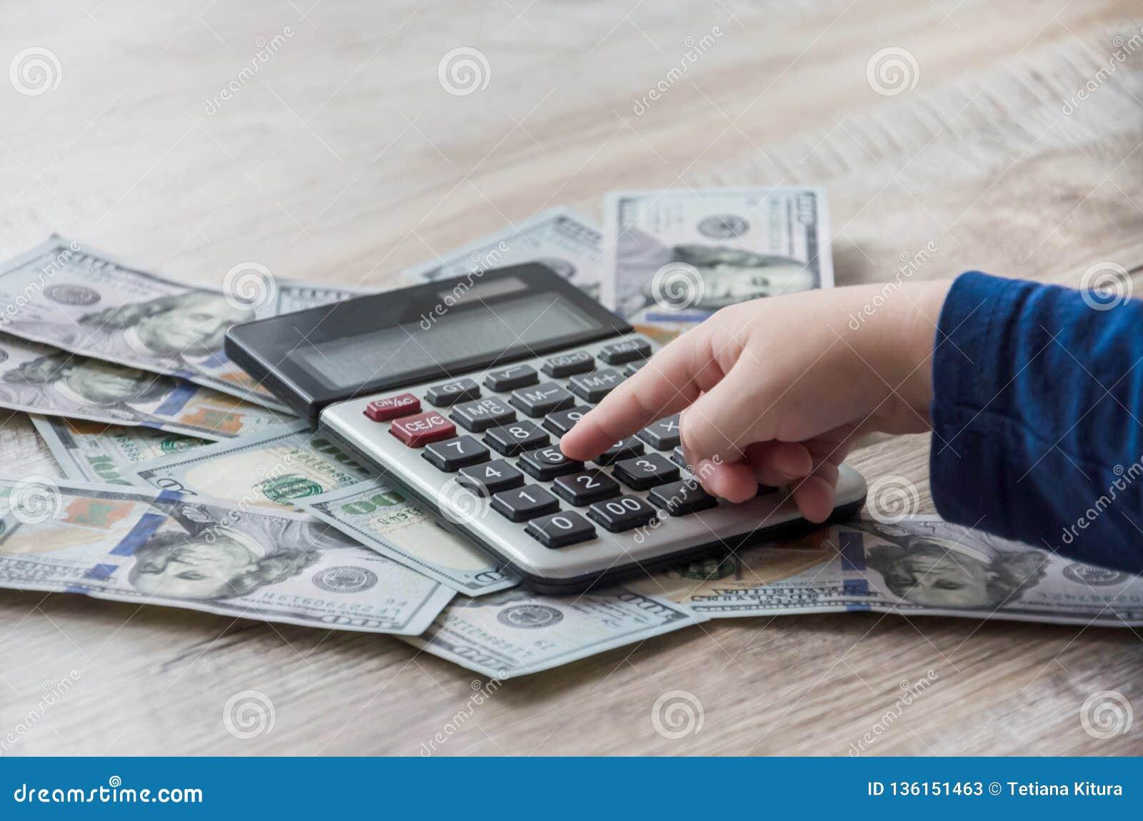 Dolary, kalkulator i ręka na drewnianym stole,