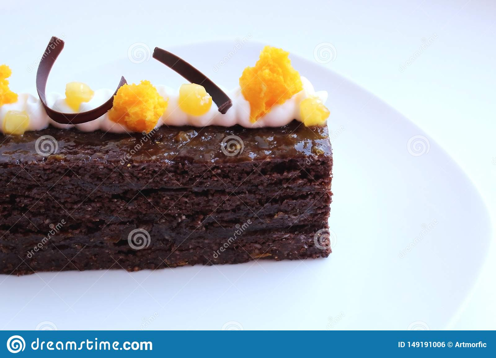 Dolce del Torte di Sacher con i pezzi dell albicocca e decorazione arancio della spugna di microonda sul piatto bianco