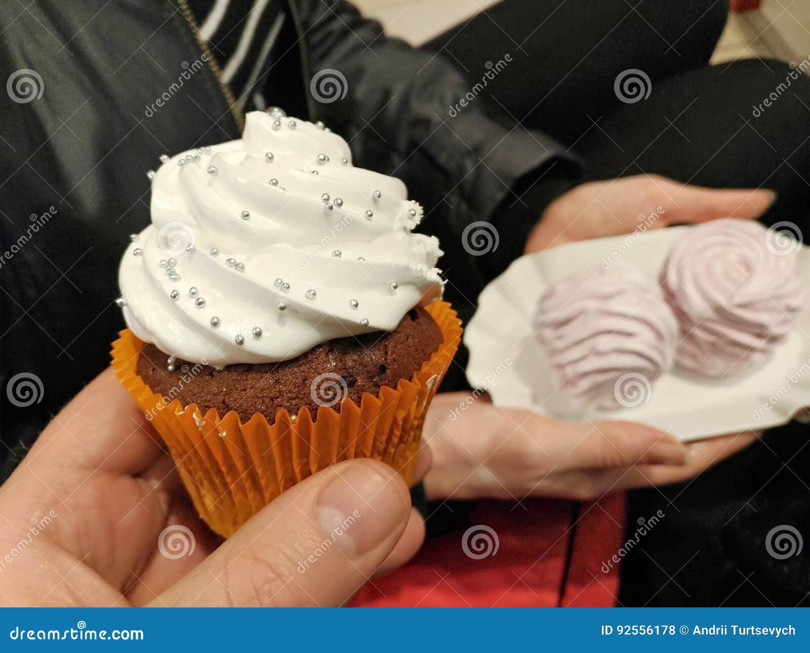 Dolce di cioccolato con crema bianca nel braccio, primo piano