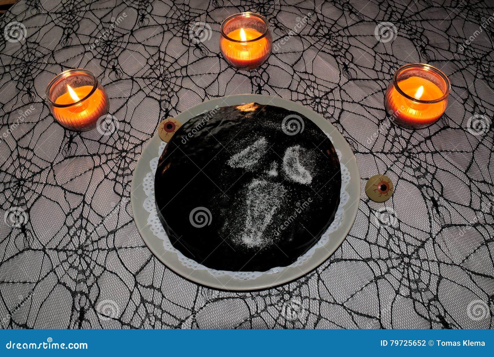 Dolce di Halloween sulla tovaglia della ragnatela con le candele