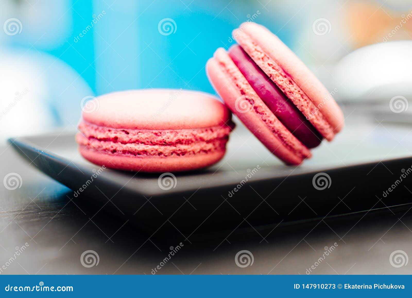 Dolce, macarons freschi con caff? in una tazza blu su una tavola nera