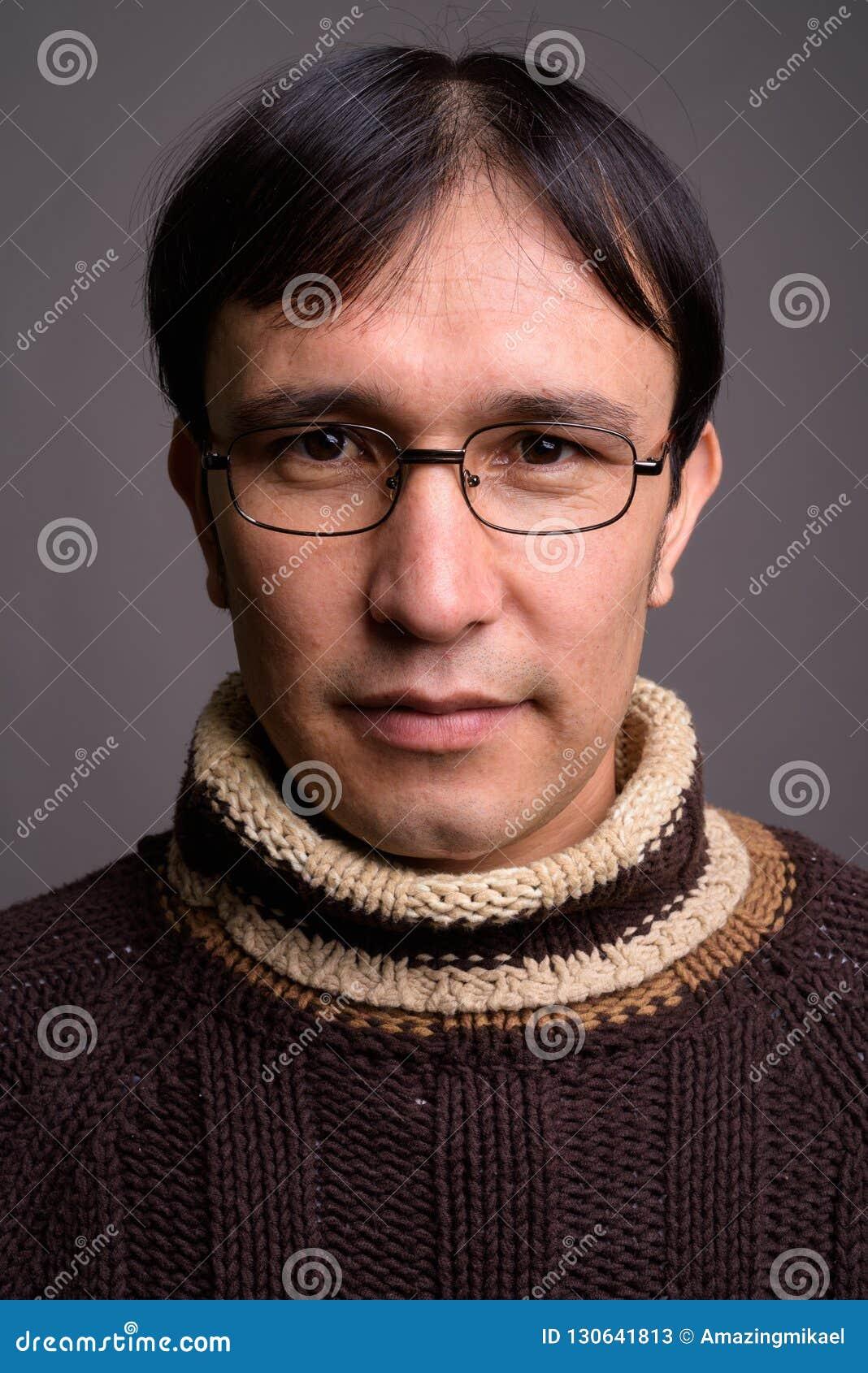 Dolcevita d uso del giovane uomo asiatico del nerd contro il BAC grigio