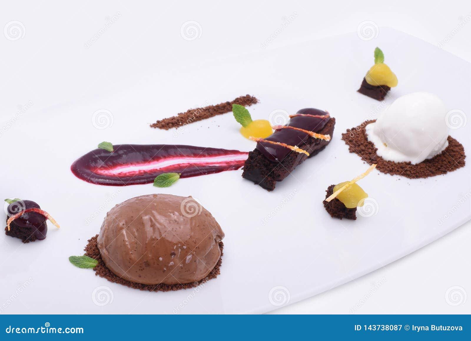 Dolci deliziosi - dolce di cioccolato, caramelle della frutta e palle del gelato su un piatto bianco
