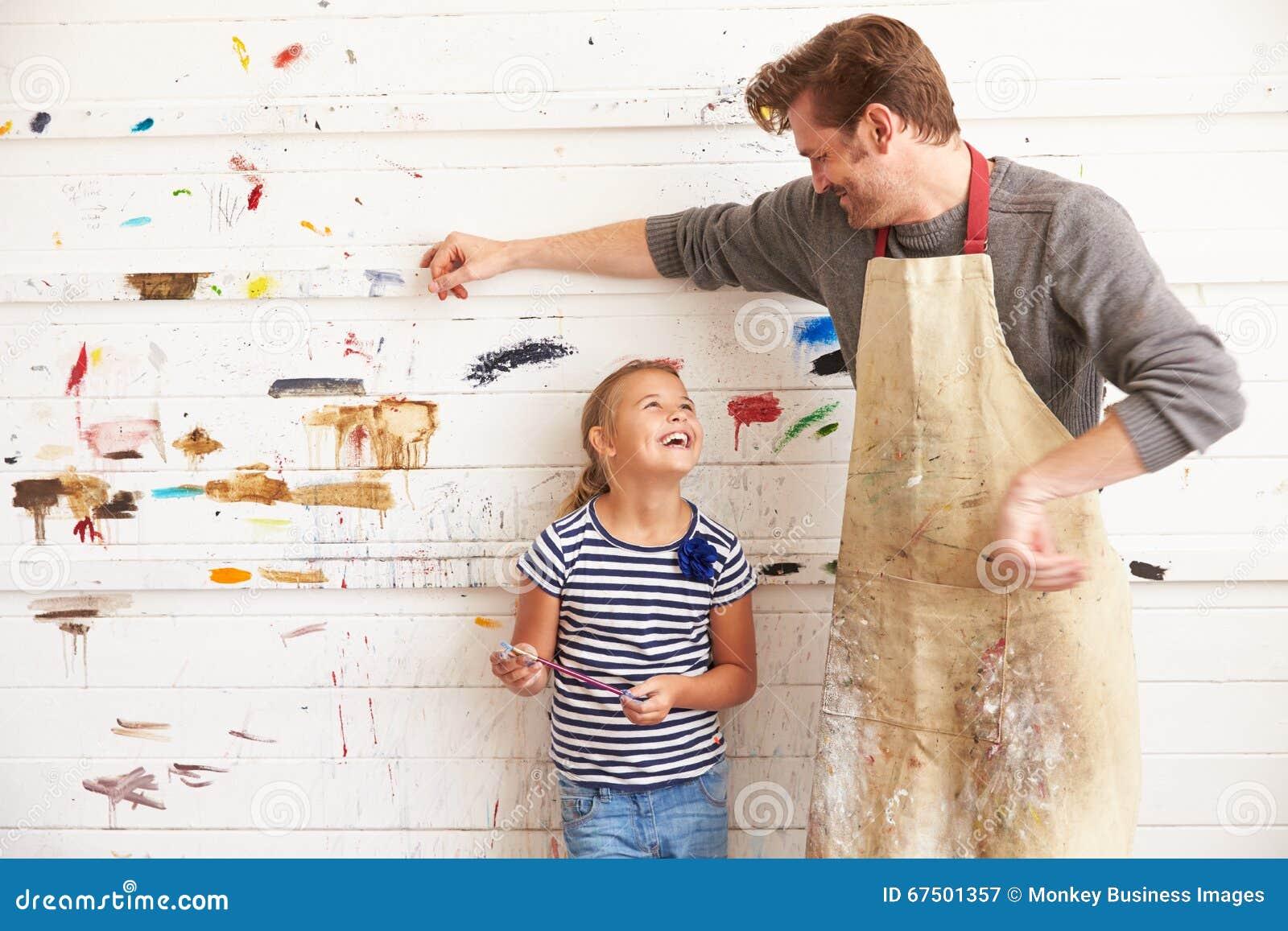 Dold vägg för faderAnd Daughter Against målarfärg i Art Studio