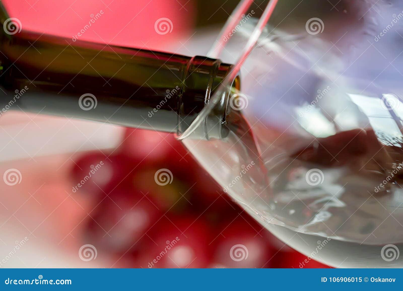 Dolewania czerwone wino w szkło przeciw winogronu