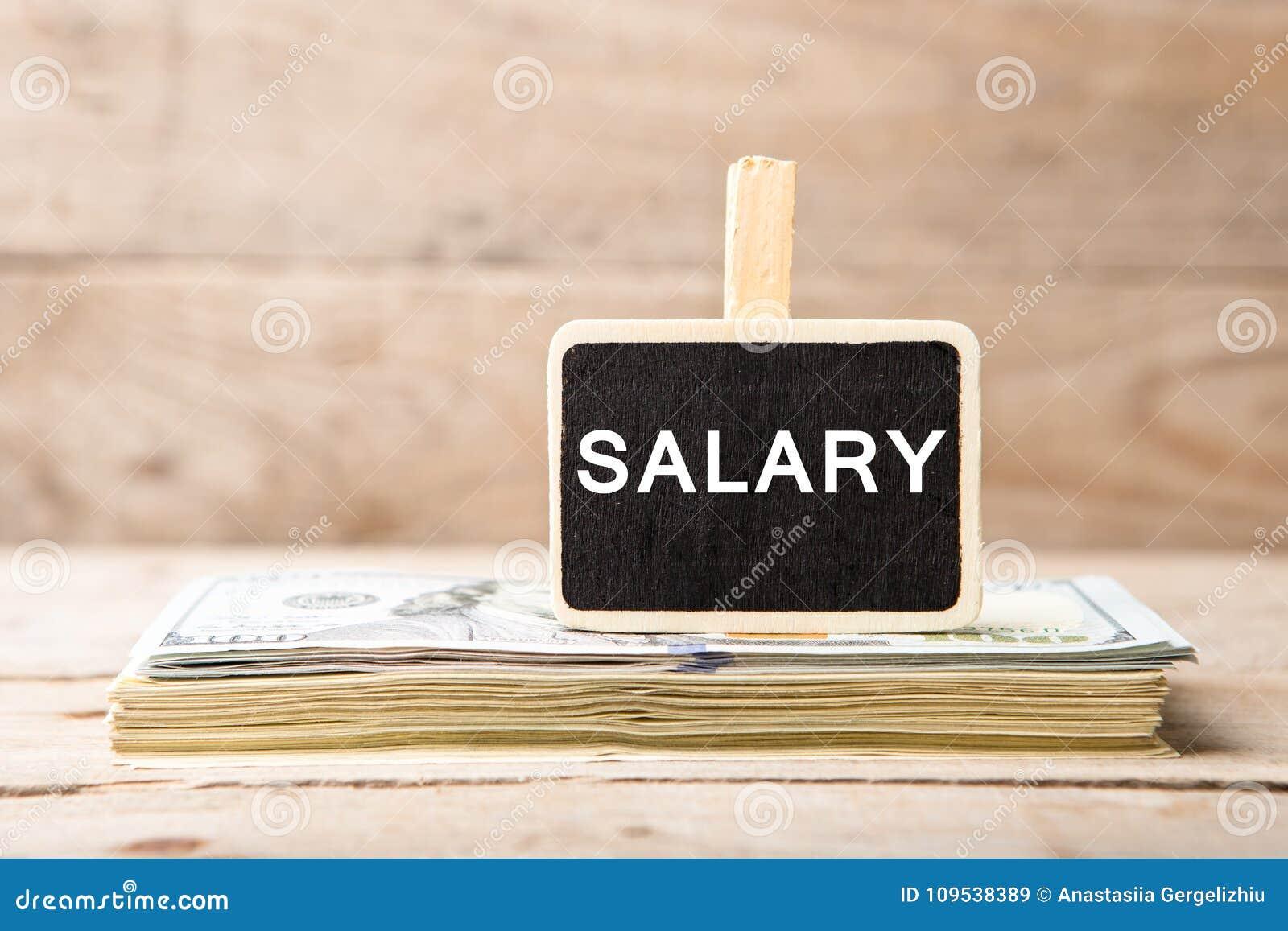 Dollar bills, blackboard with text & x22;SALARY& x22;