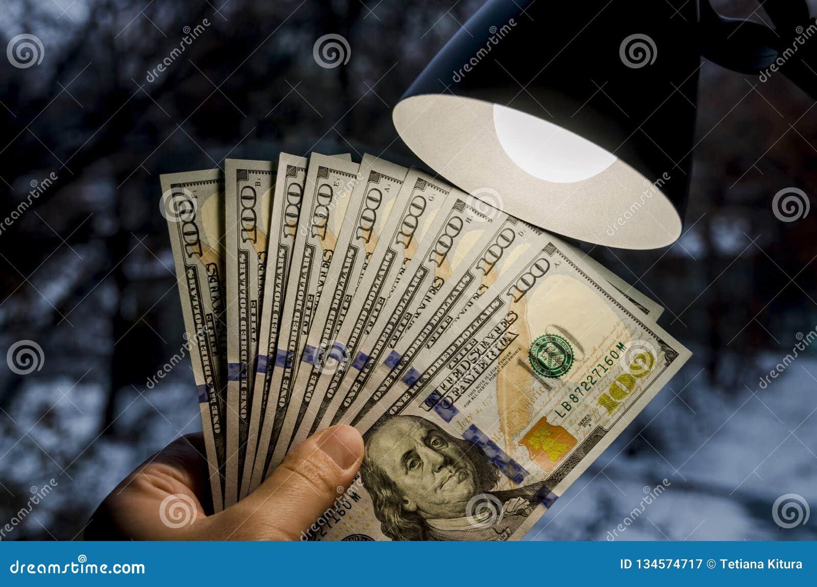 Dollar i hand och en tabelllampa