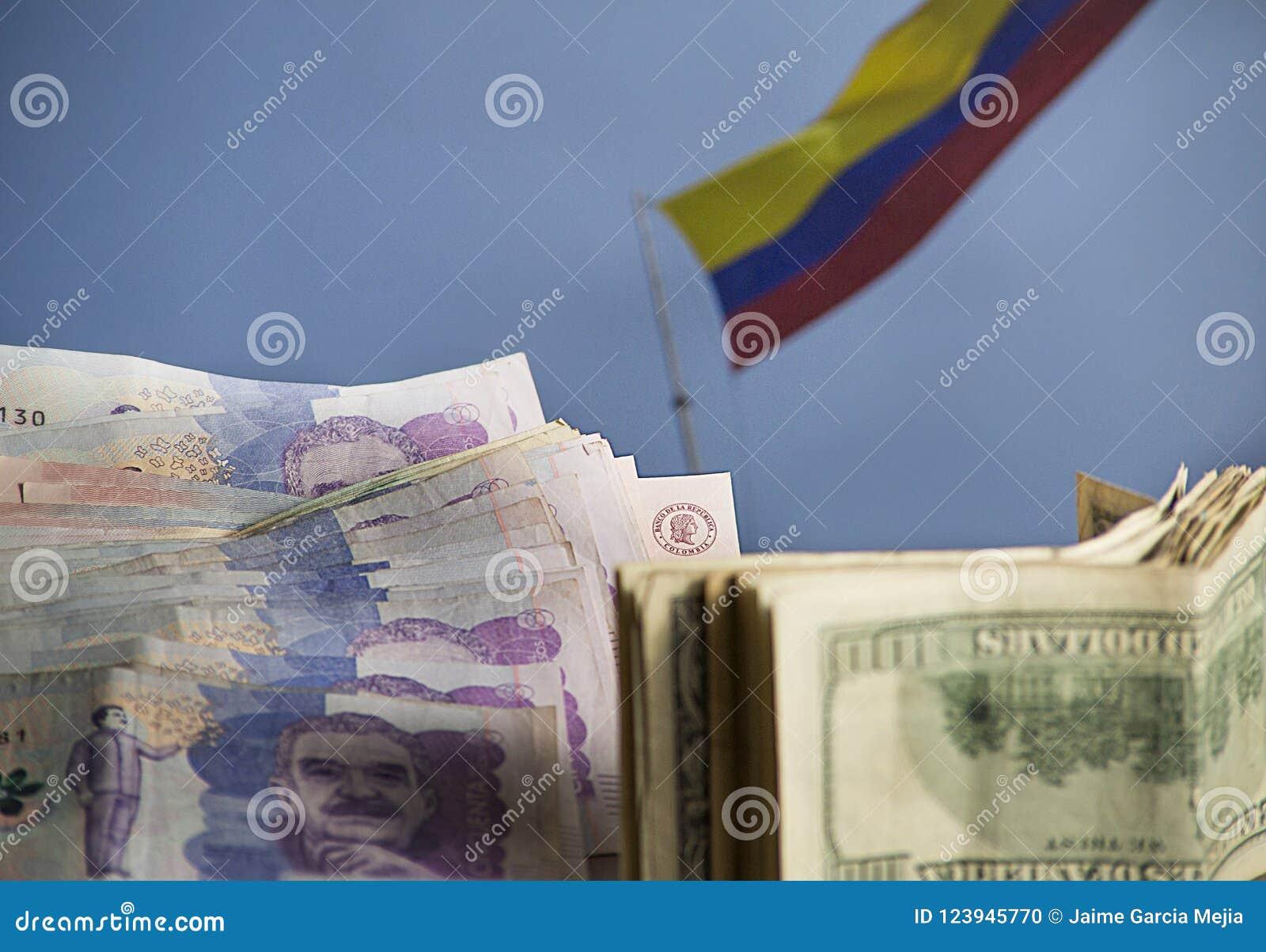 Dollar och colombianska pengar med den colombianska flaggan som vinkar i bakgrunden