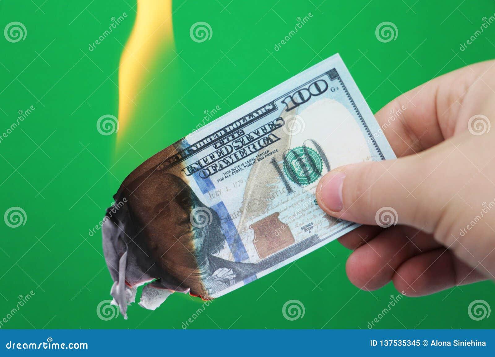 100 dollar som bränner på en grön bakgrund Begrepp av nedgång i ekonomi och förlust