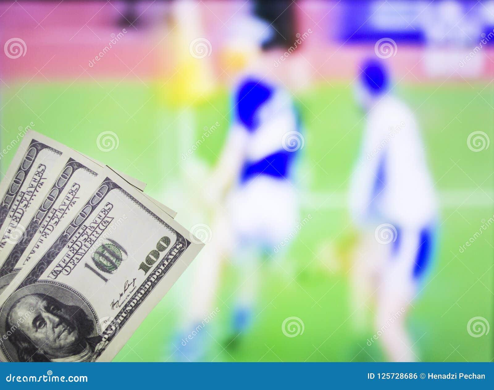 Dollari dei soldi sui precedenti di una TV su cui lo sport è indicato nel gioco di lancio, gli sport che scommettono, dollari