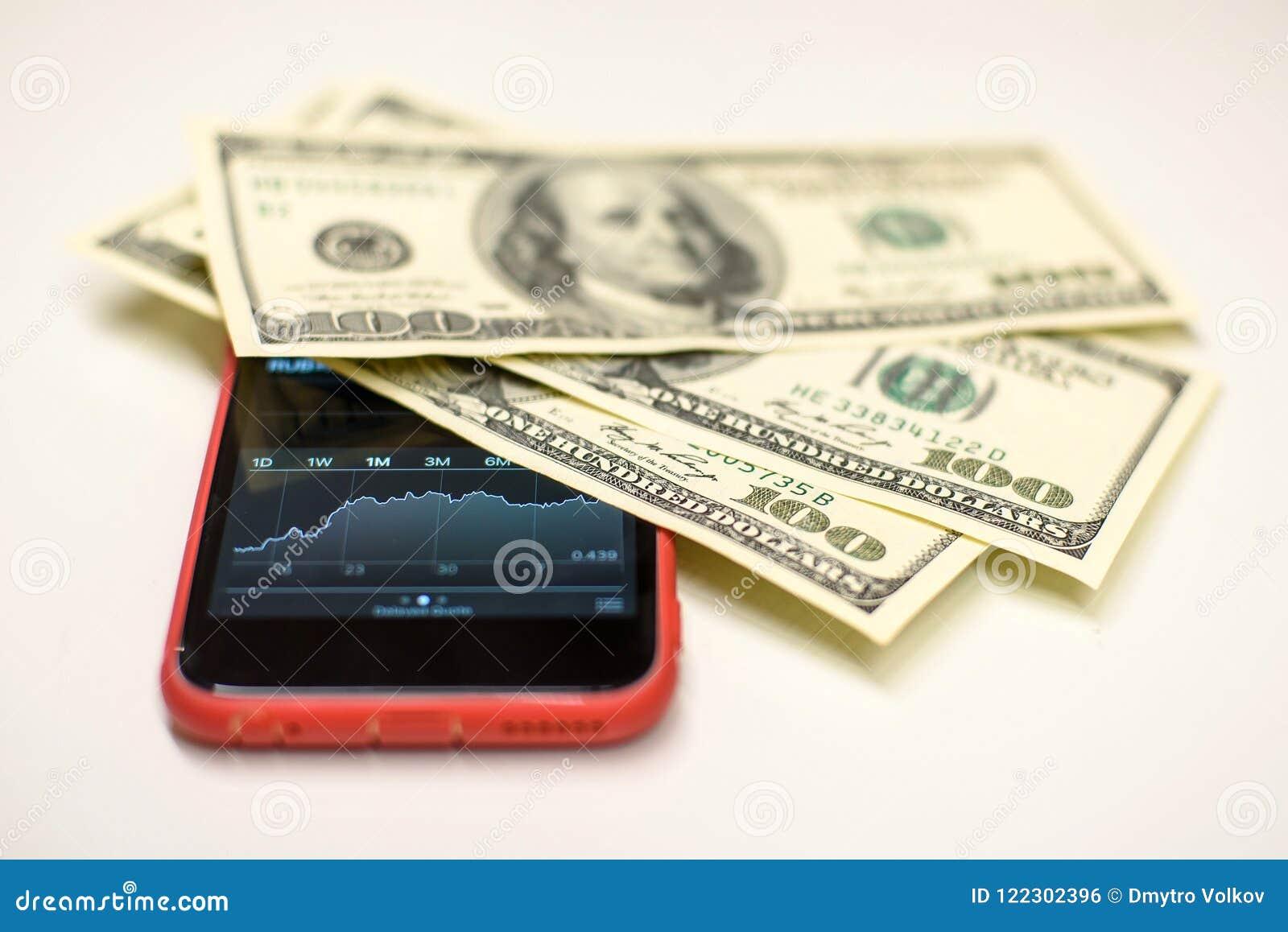 Dollarrekeningen over een smartphone met voorradengrafiek