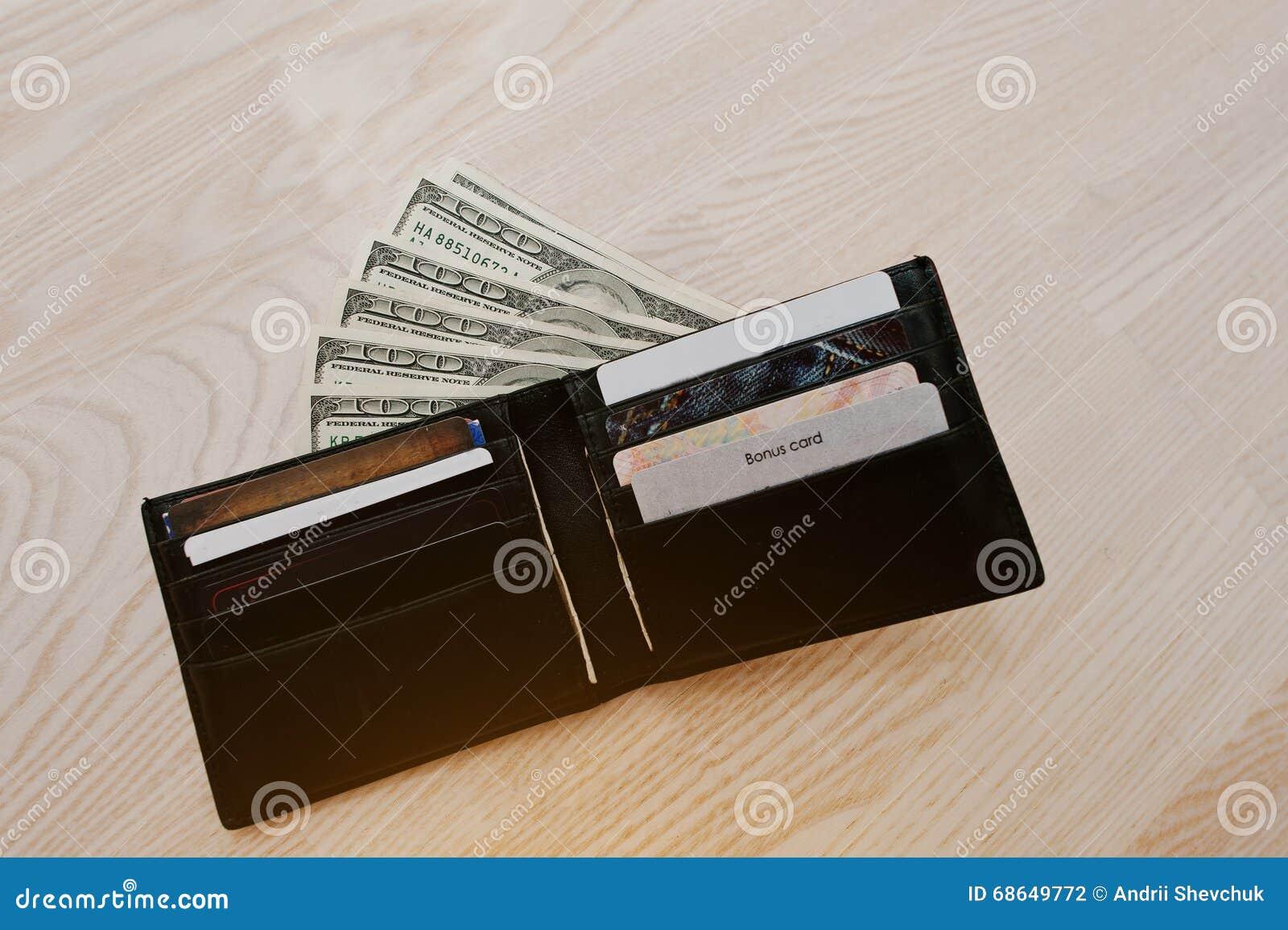Dollars avec des cartes de crédit dans le portefeuille en cuir noir