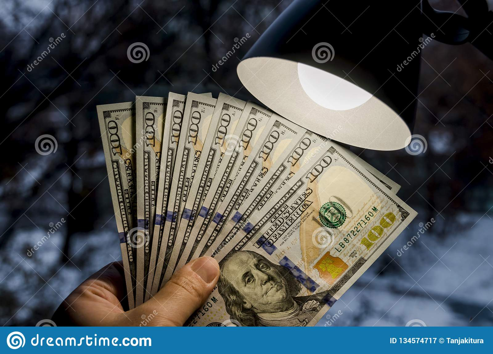 Dollars in hand and a table lamp