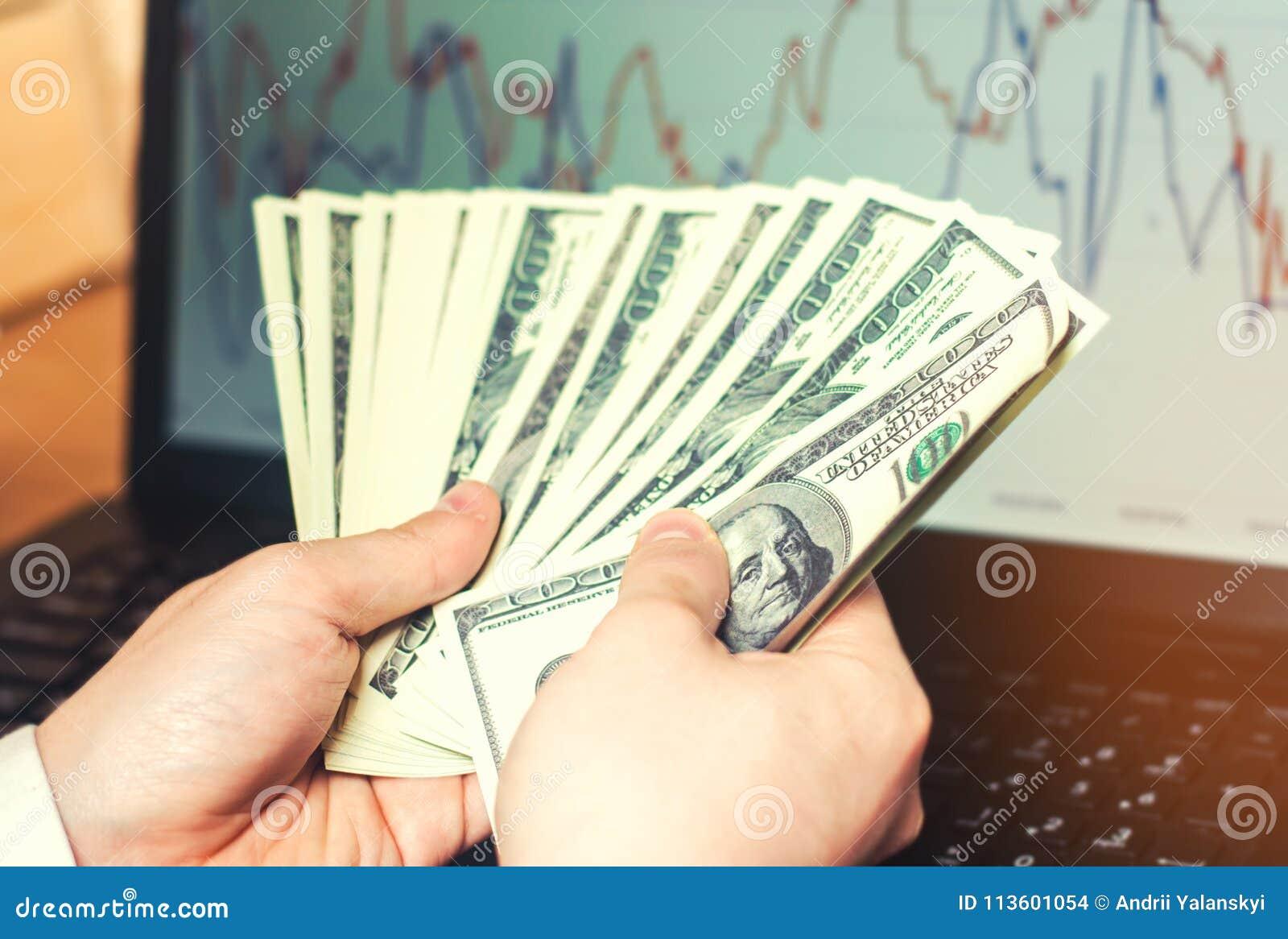 Dollars in handen op computerachtergrond, het concept het kopen op Internet, investering, succes, het gokken Internet-fraude, bee