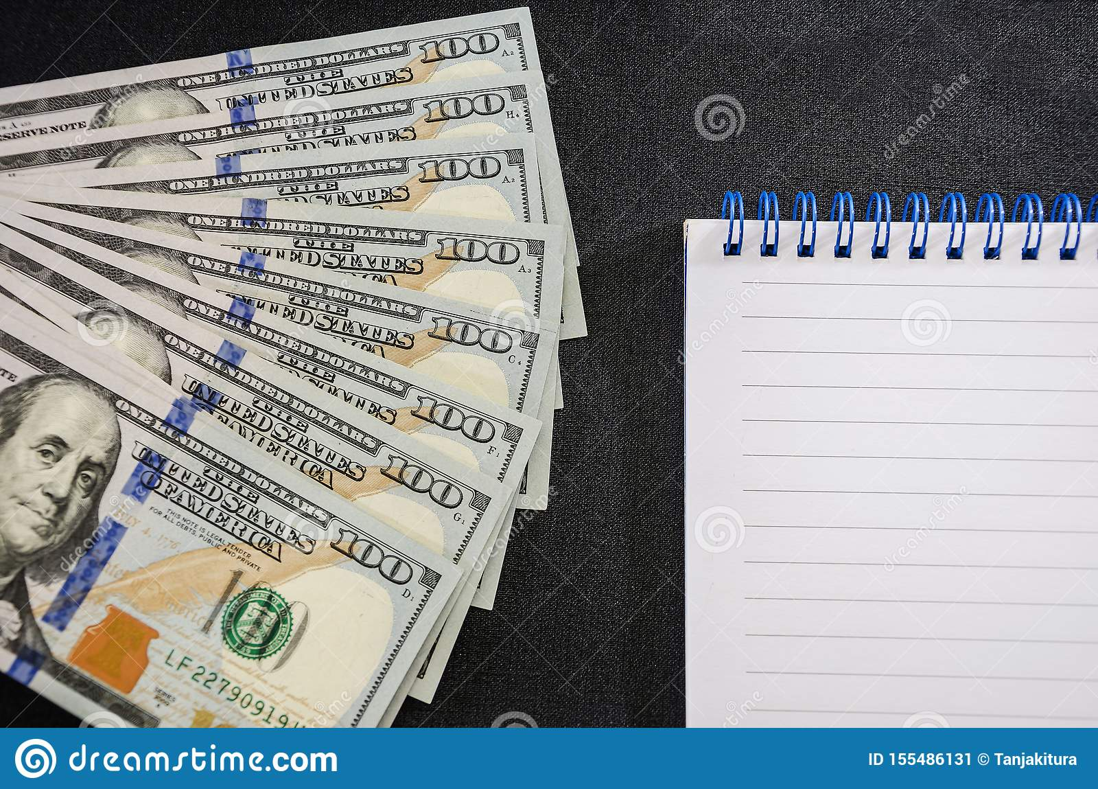 Dollars and notebook on a black background. Close-up. Place for text.
