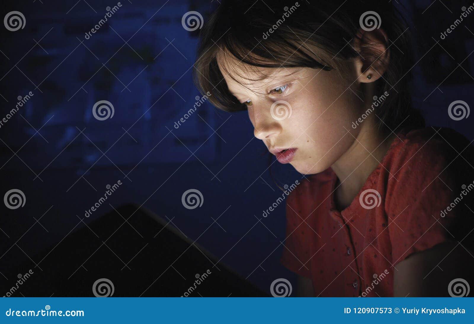 Dolly geschoten Kaukasisch meisje in bed het spelen tablet in Internet in donkerblauw licht onder blacket