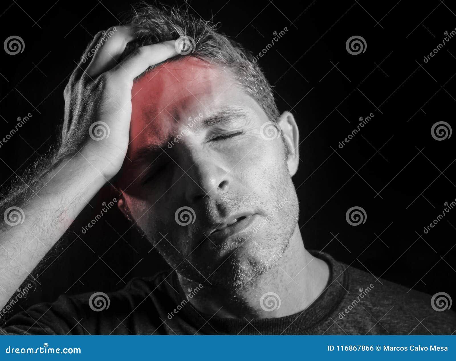 Dolor de cabeza sufridor joven del hombre atractivo y triste con la mano en su cabeza del tempo en la tensión que mira negro dese