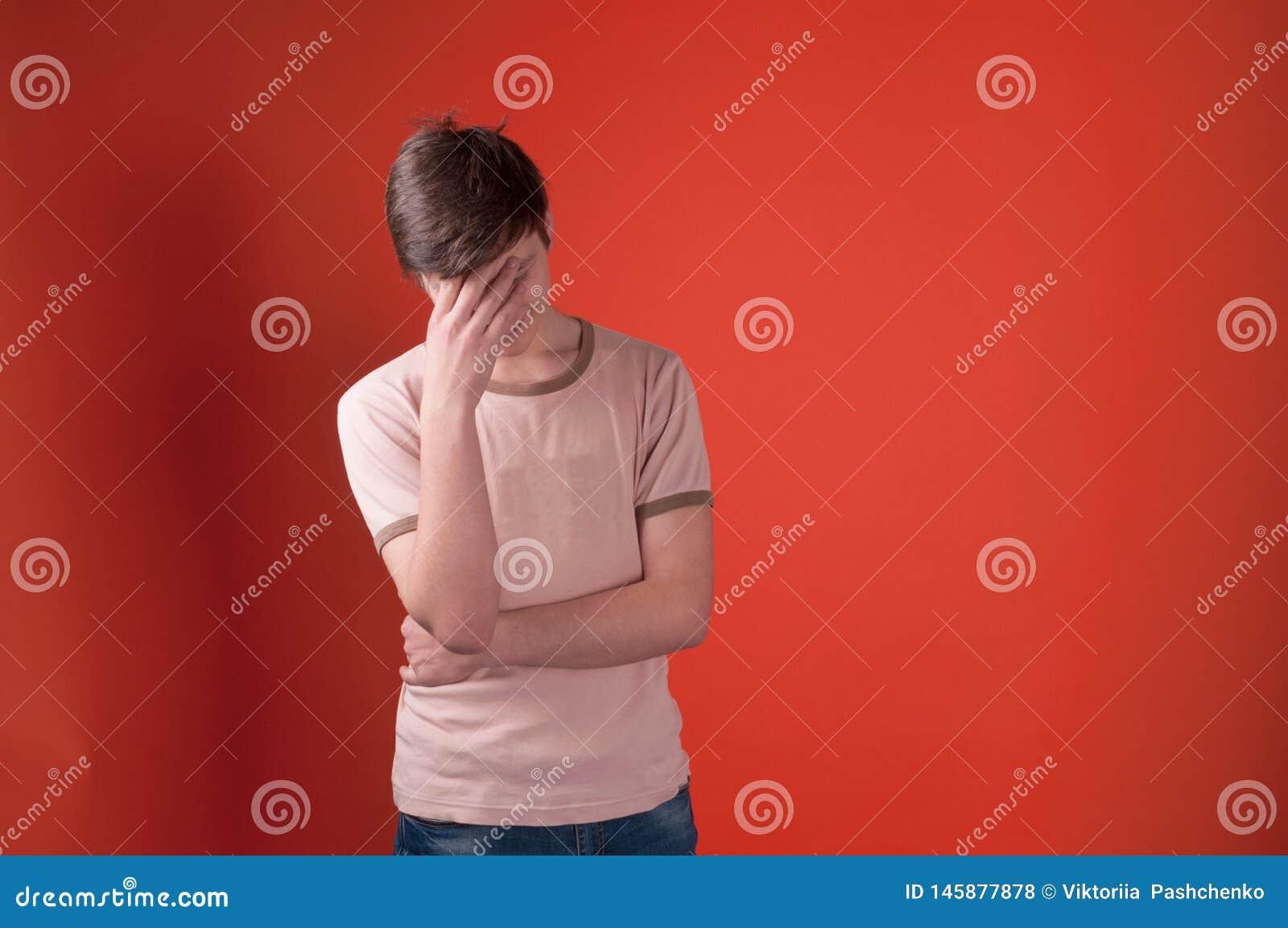 Dolor de cabeza triste de la sensación del hombre joven en la situación beige de la camiseta con la mano en la frente
