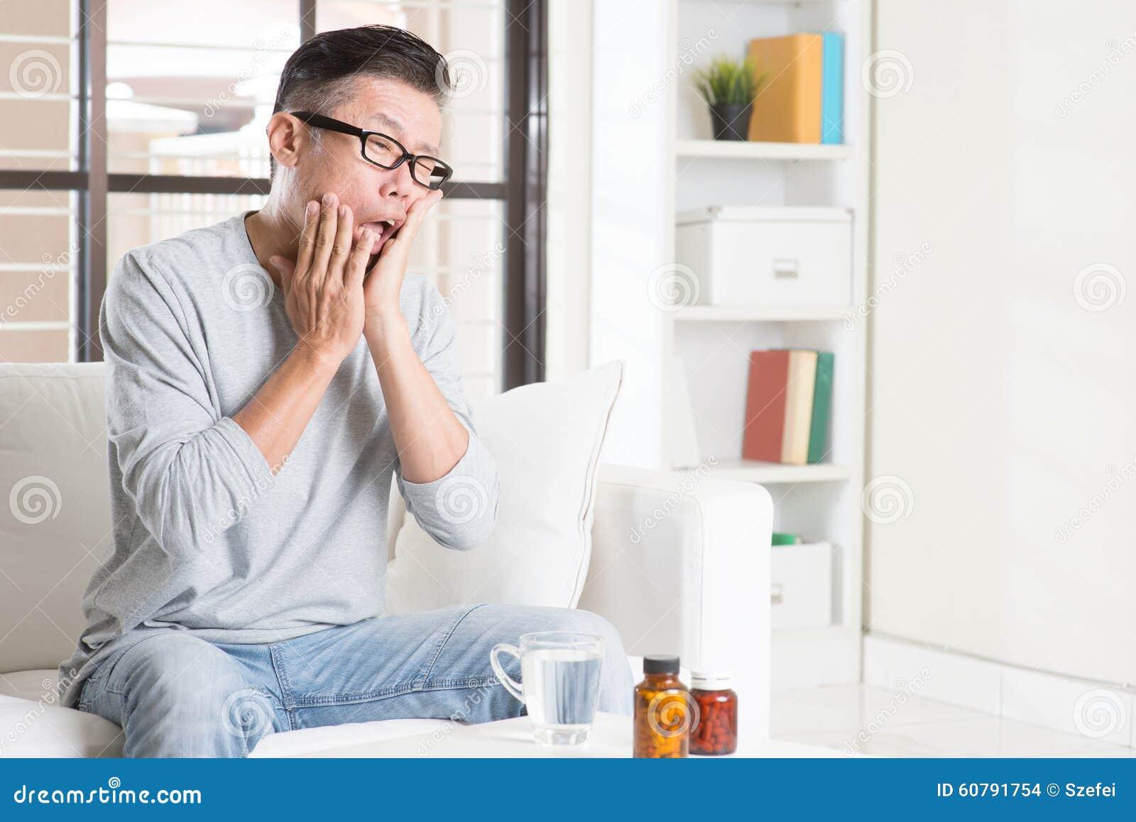 Dolor de muelas asiático maduro del hombre