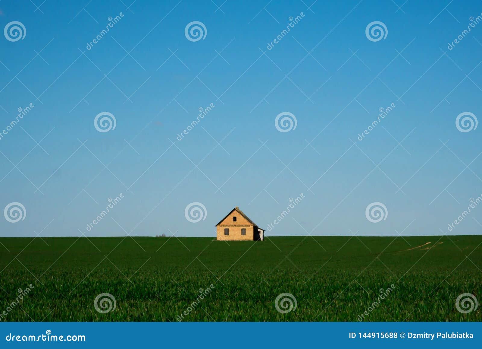 Dom na zielonym niebieskim niebie i polu