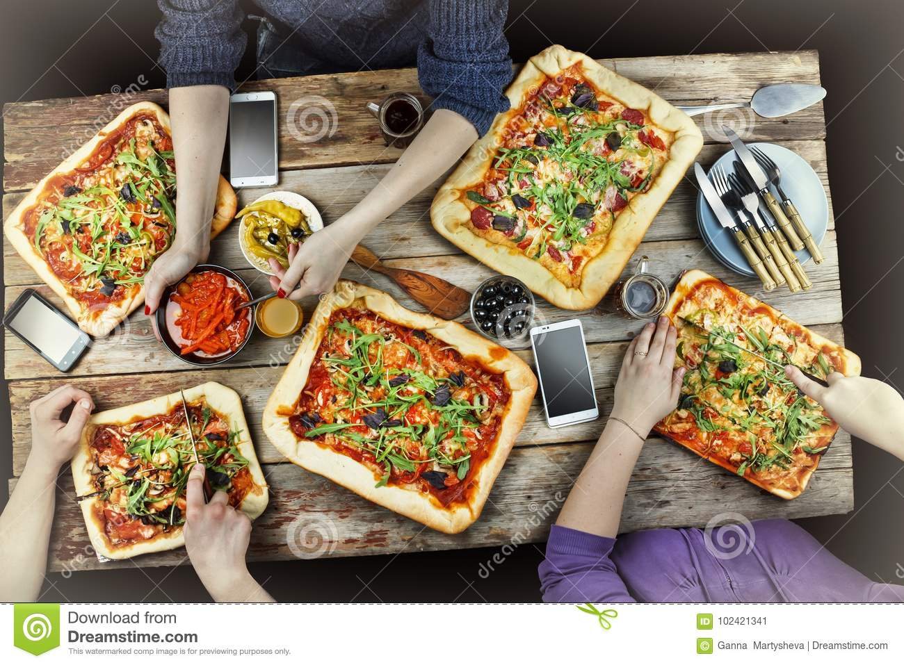 Cutting pizza. Domestic food and homemade pizza. Enjoying dinner with friends. Top view of group of people having dinner together