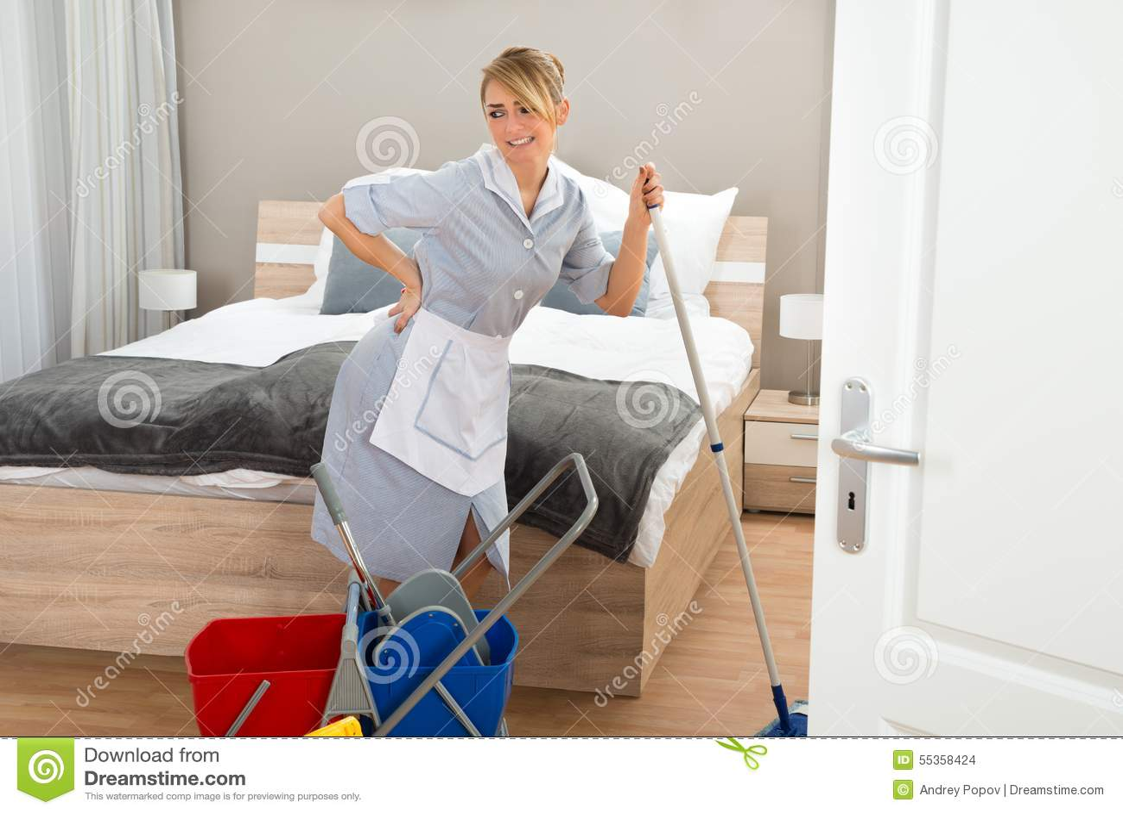 Domestica che soffre dal mal di schiena mentre pulendo camera di albergo