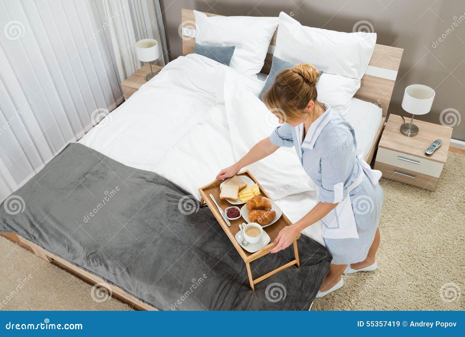 Domestica con la prima colazione che tiene sulla tavola del vassoio