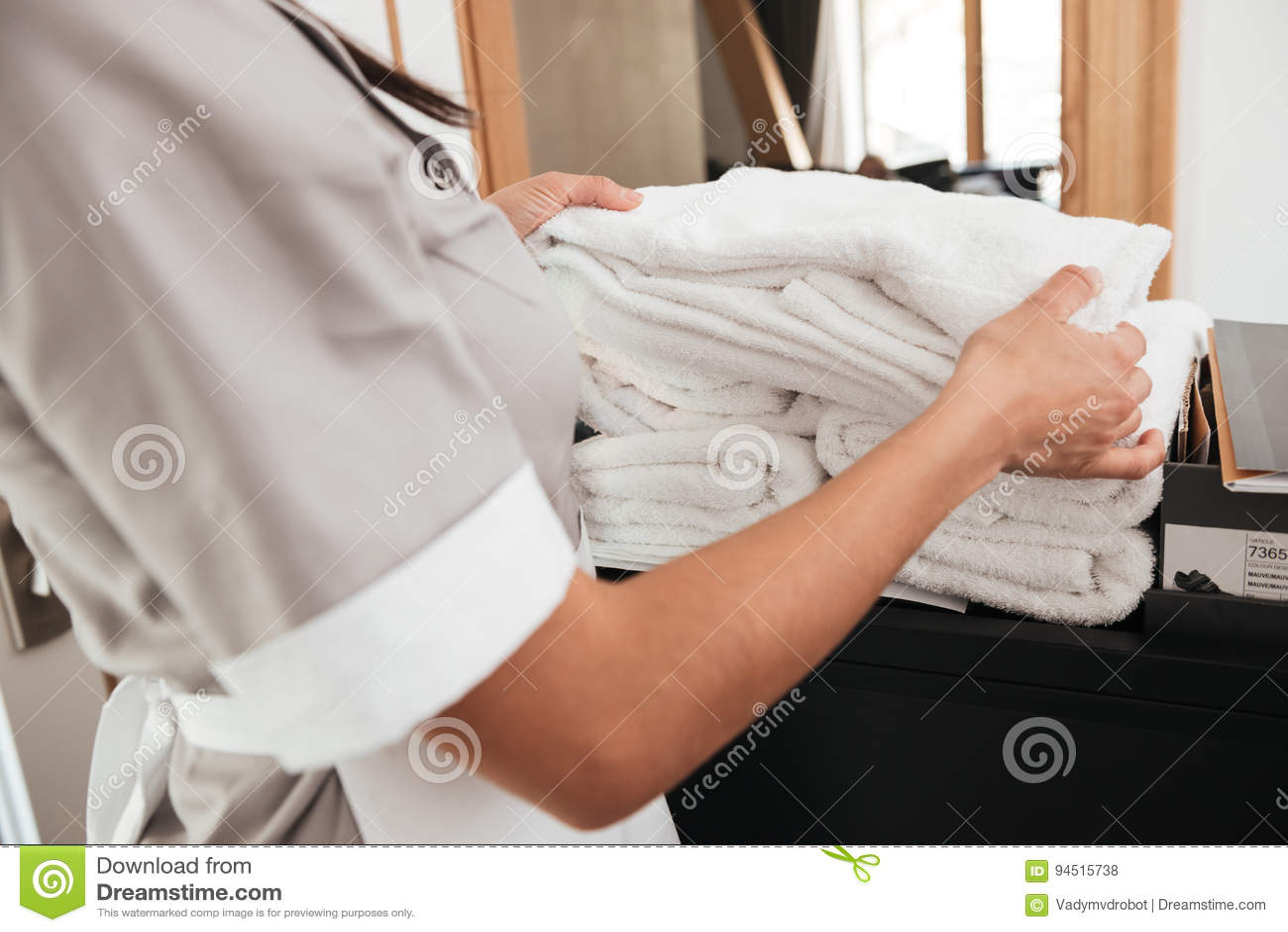 Domestique d hôtel prenant les serviettes fraîches d un chariot de ménage