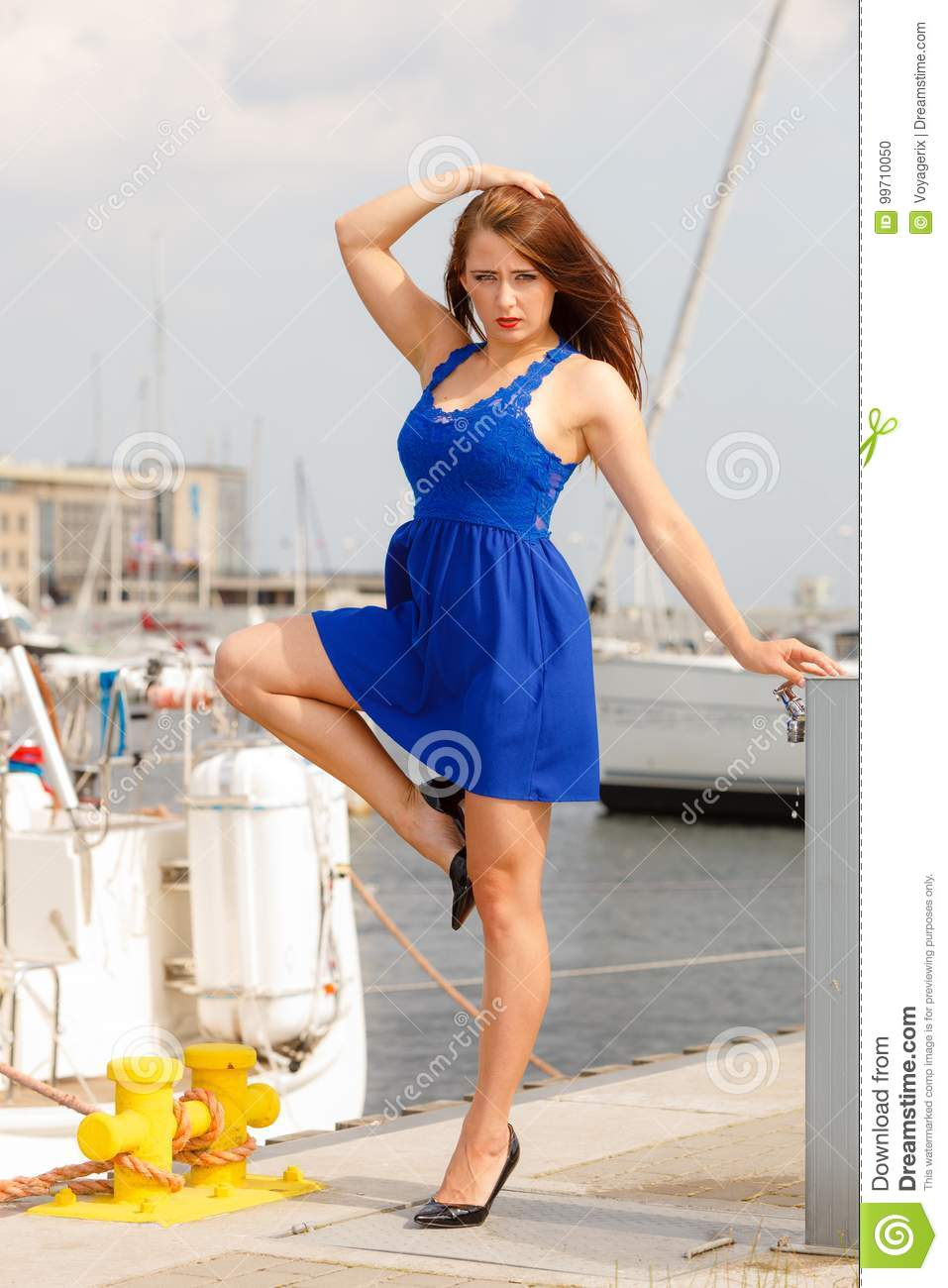 a6e1141a Dominant feminist woman wearing high heels and short blue dress, standing  one leg on big industrial bolt in marina.