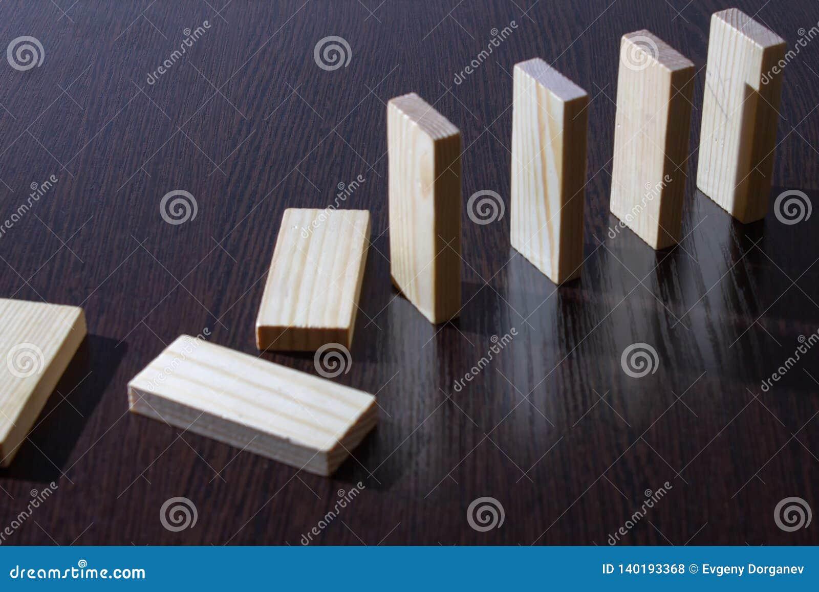 Dominobrickakuber från lönn på en mörk tabell